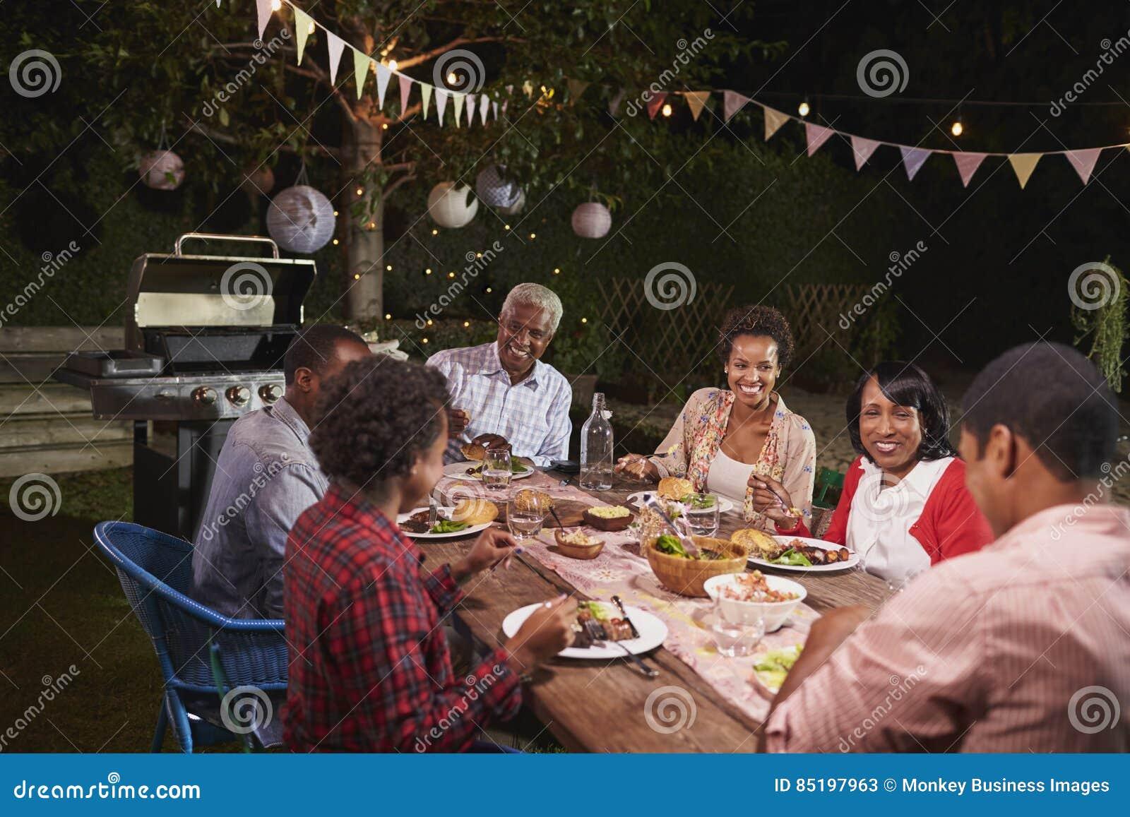 Svart familj för vuxen människa som tillsammans tycker om matställen i deras trädgård