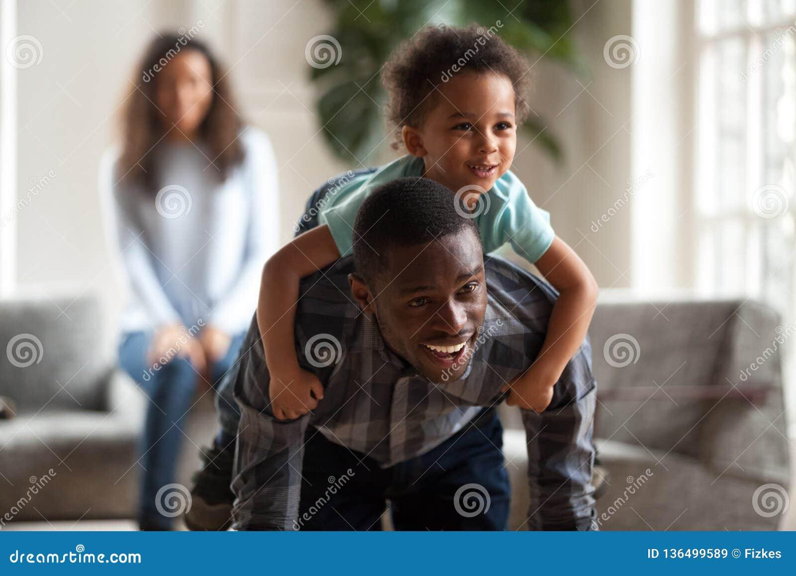 Svart farsa som ger den bärande sonen för barnridtur på axlarnaritt på tillbaka