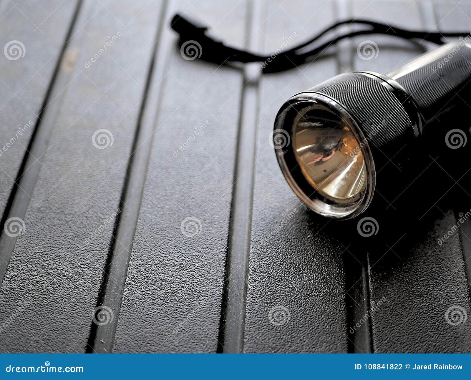 Svart ficklampa på ojämn bakgrund