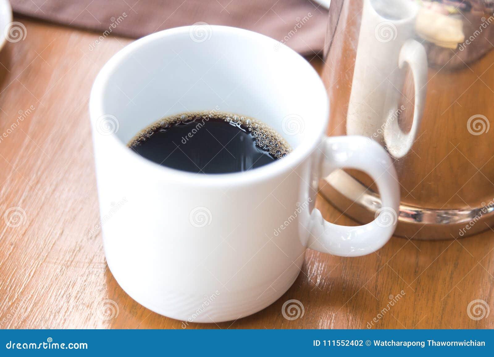 Svart kaffe i den vita koppen i morgonen
