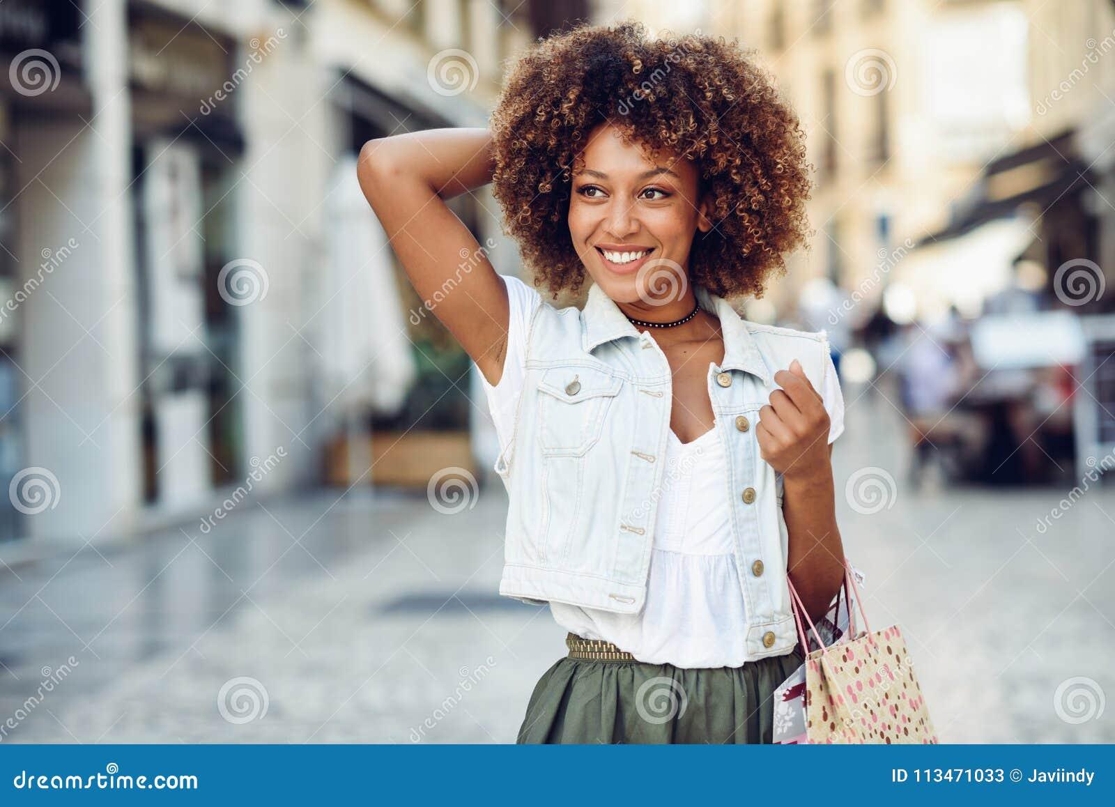 Svart kvinna afro frisyr, med shoppingpåsar i gatan