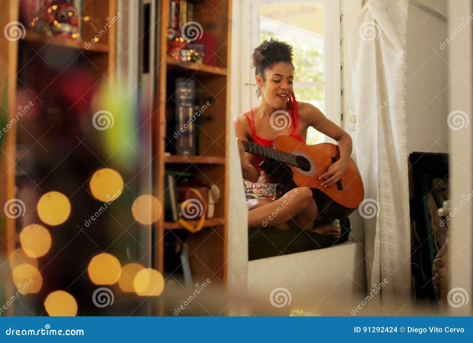 Svart kvinna som hemma sjunger och spelar gitarren