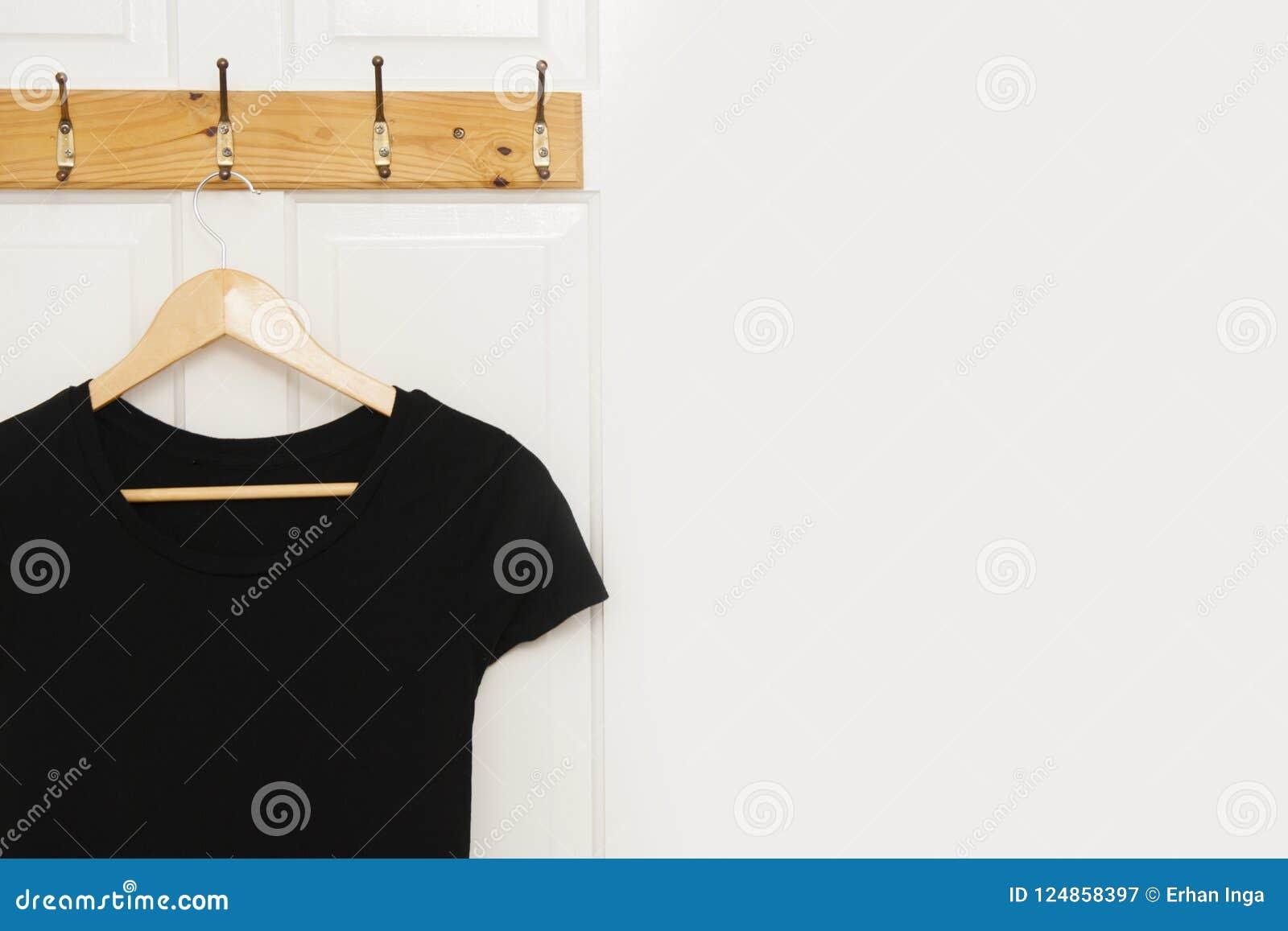 Svart kvinnaklänning på träklädhängare på den vita dörren med kopieringsutrymme isolerat Mode och daglig kläder