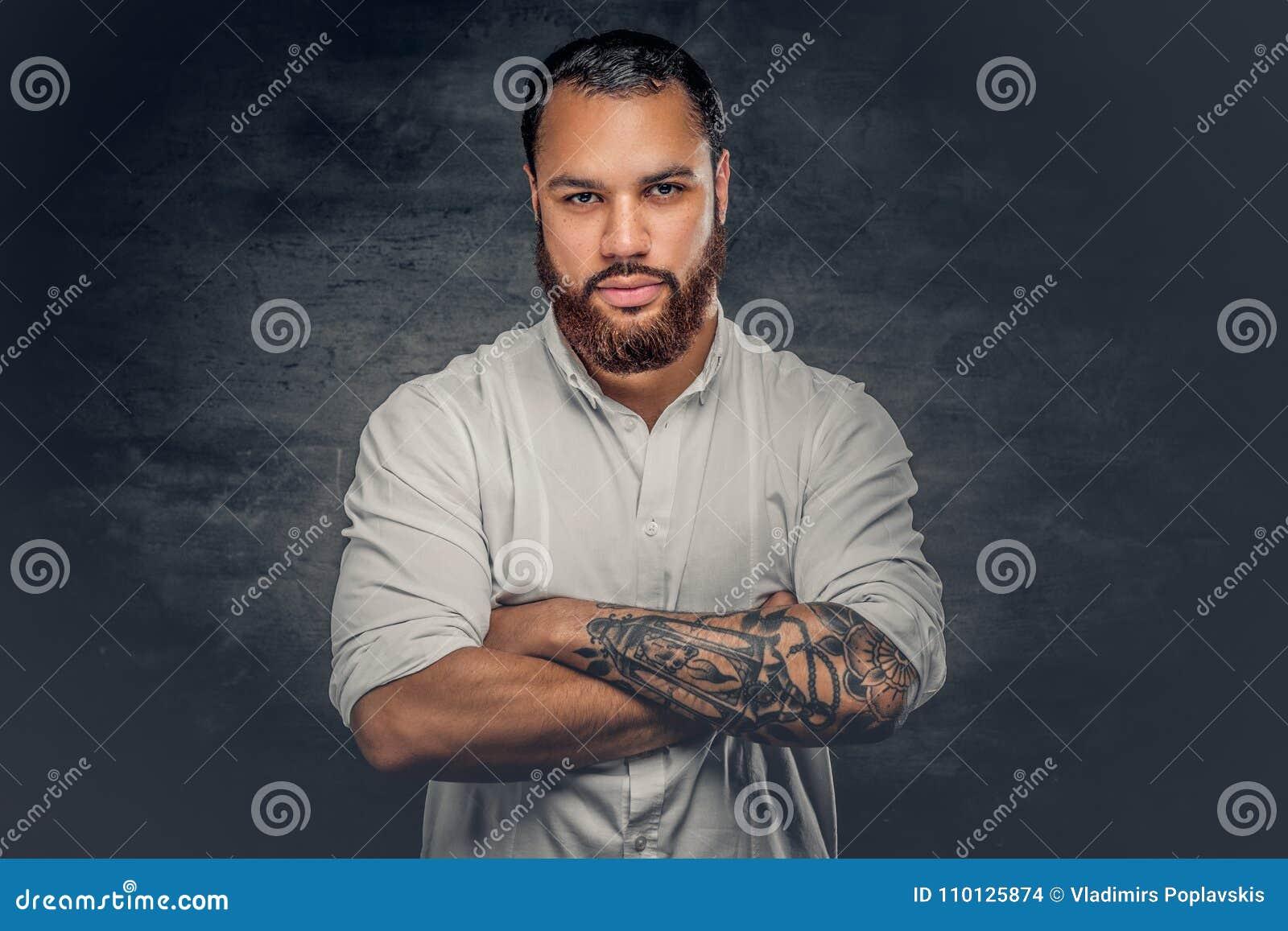 Svart man med tatueringen på armar