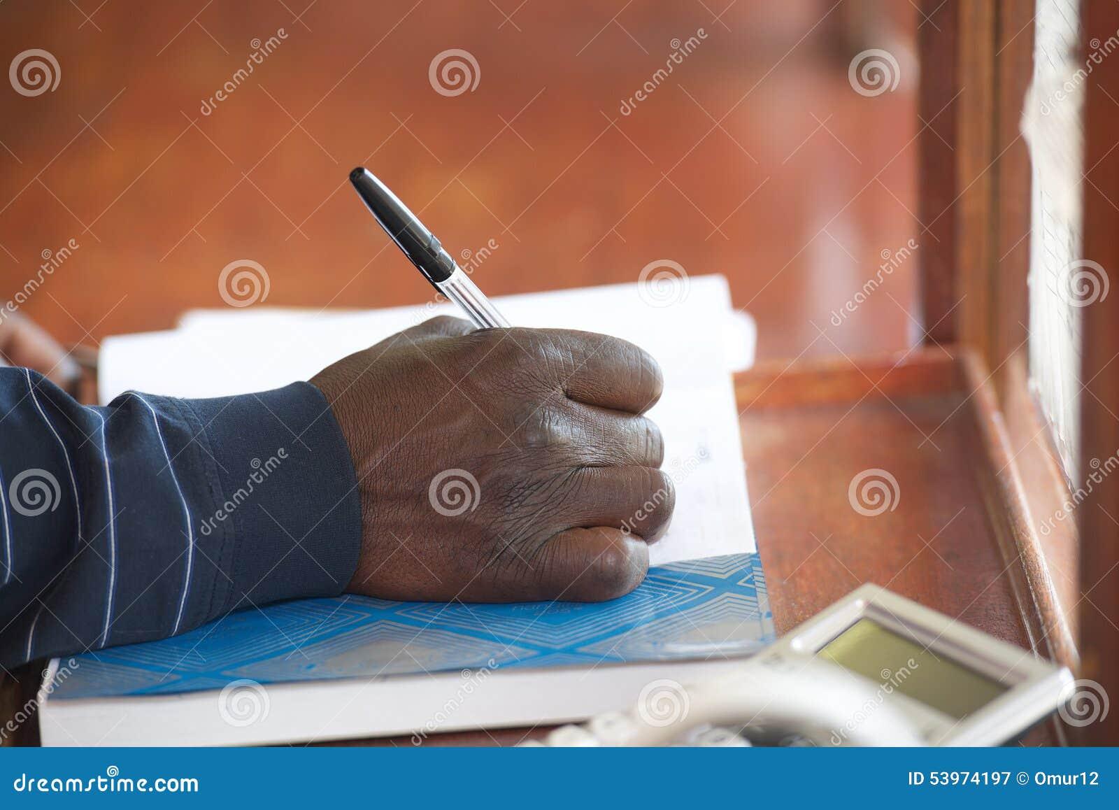Svart manhand med pennan