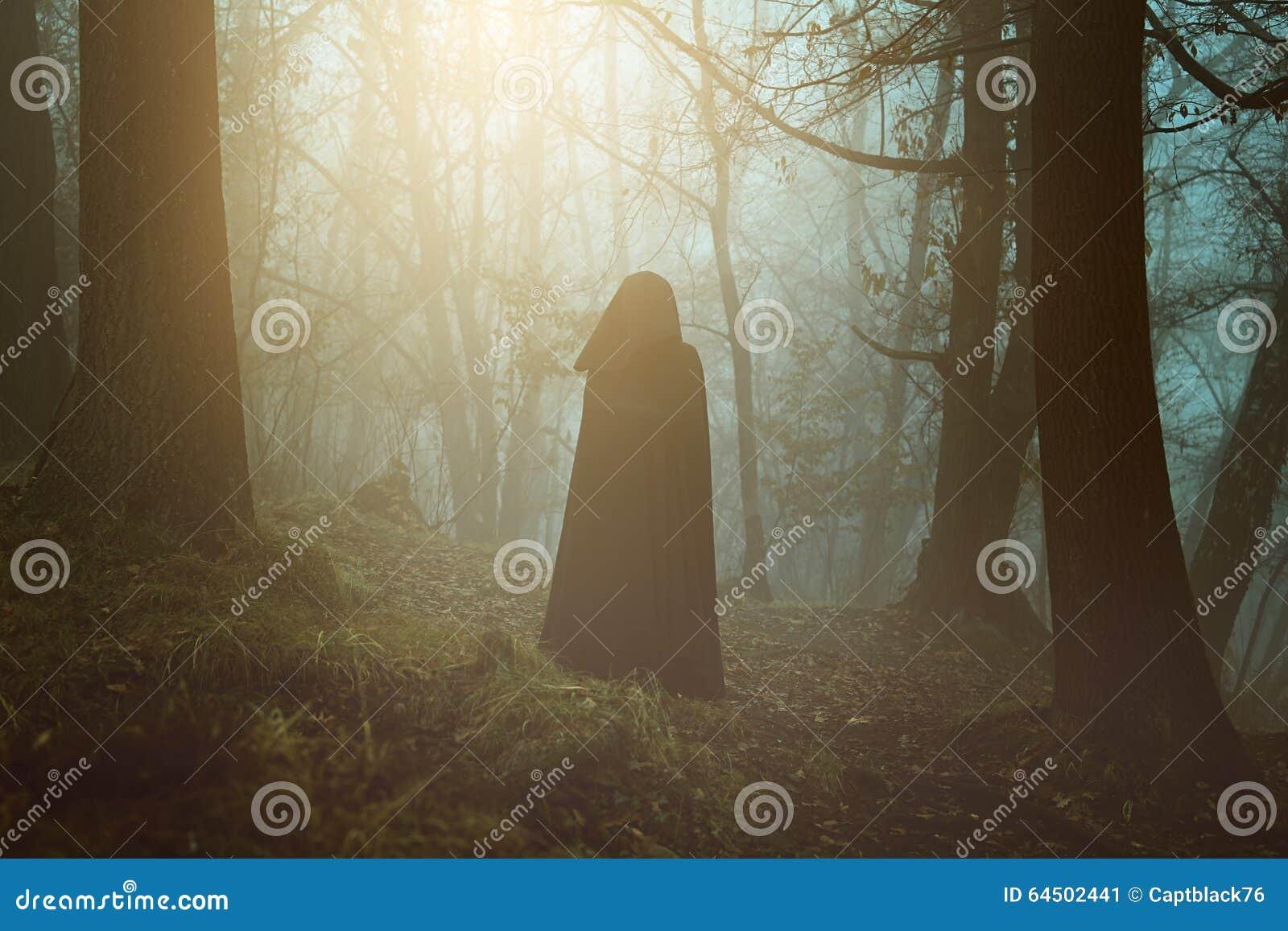 Svart med huva person i en overklig skog