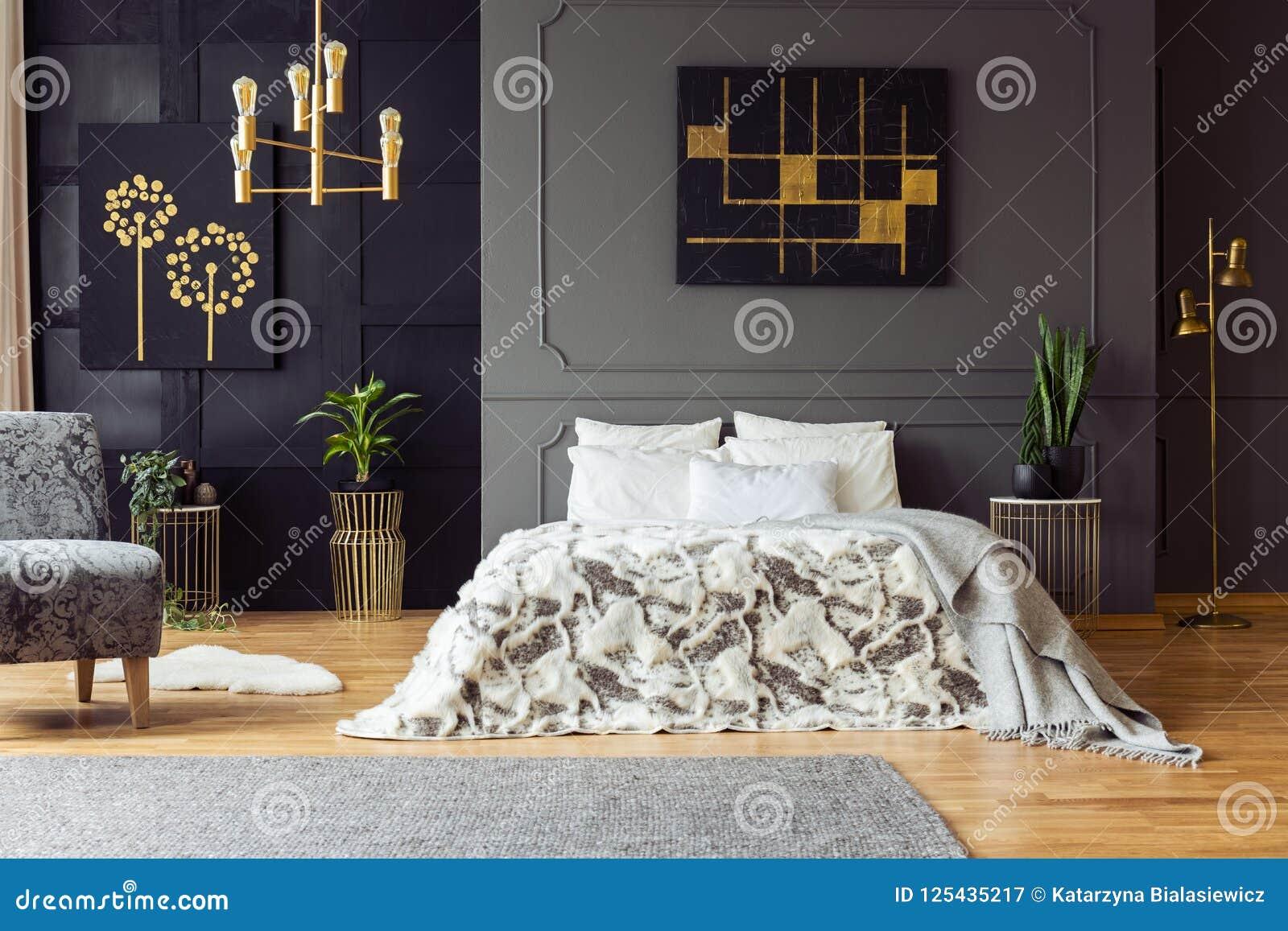 Svart och guld- affisch på ovannämnd säng för grå vägg i sovruminre med växter och fåtöljen Verkligt foto