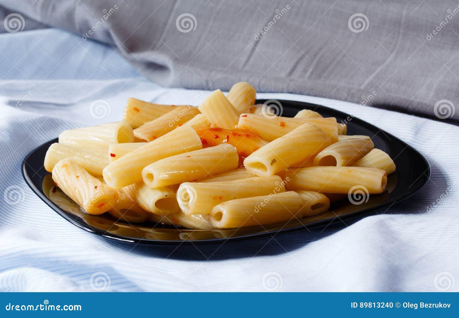 Svart platta av pasta med sås