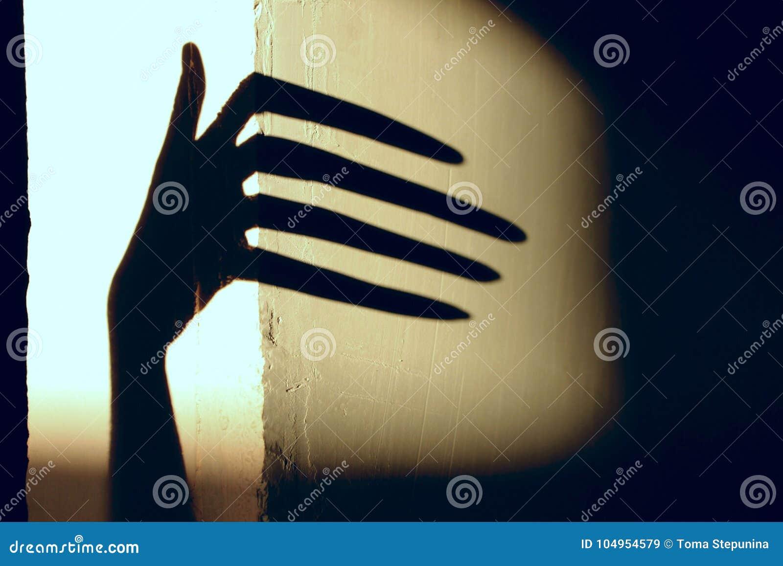 Svart skugga av en stor hand på väggen