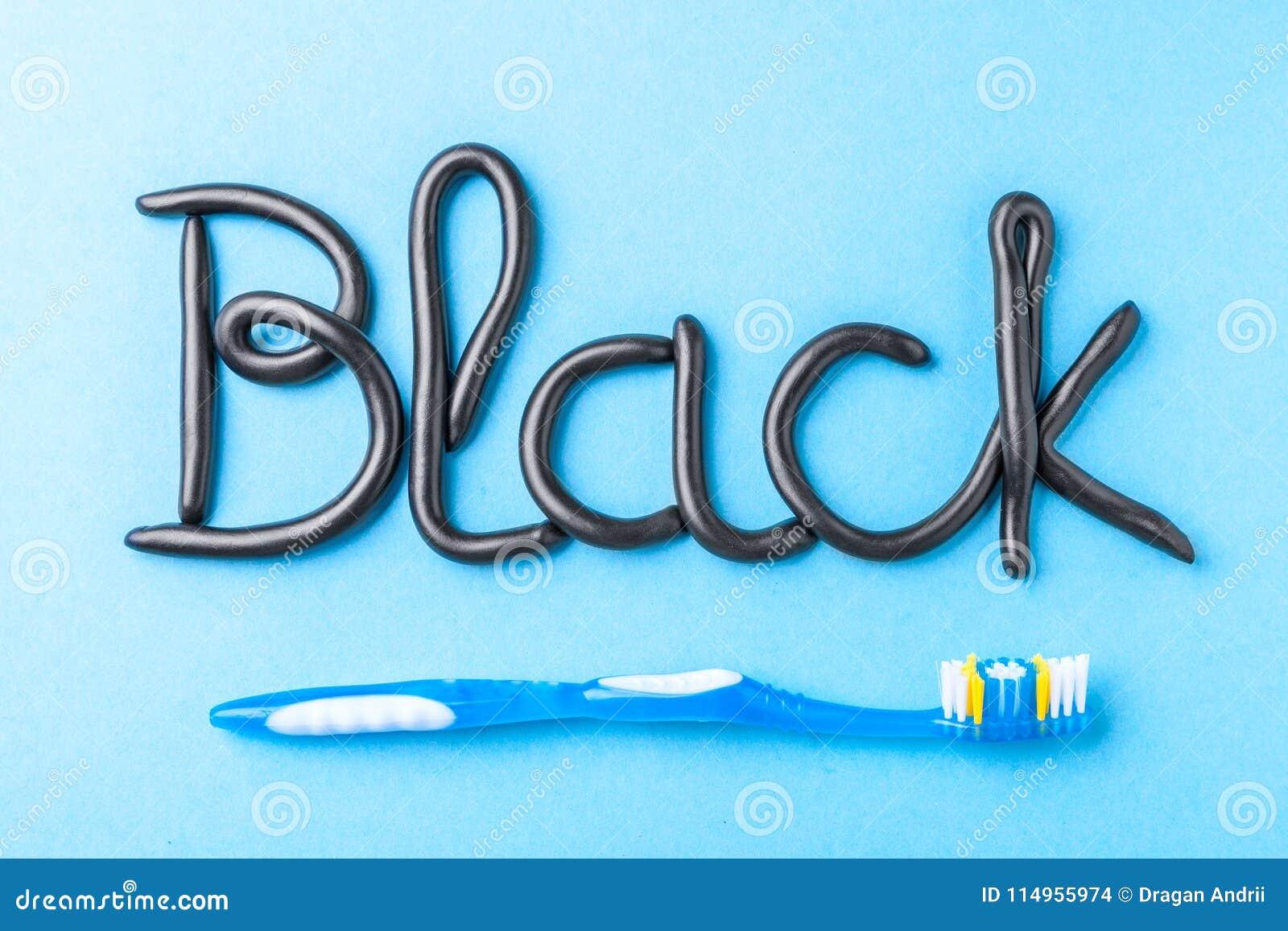 Svart tandkräm från kol för vita tänder Uttrycka SVART från tandkräm och tandborsten på blått