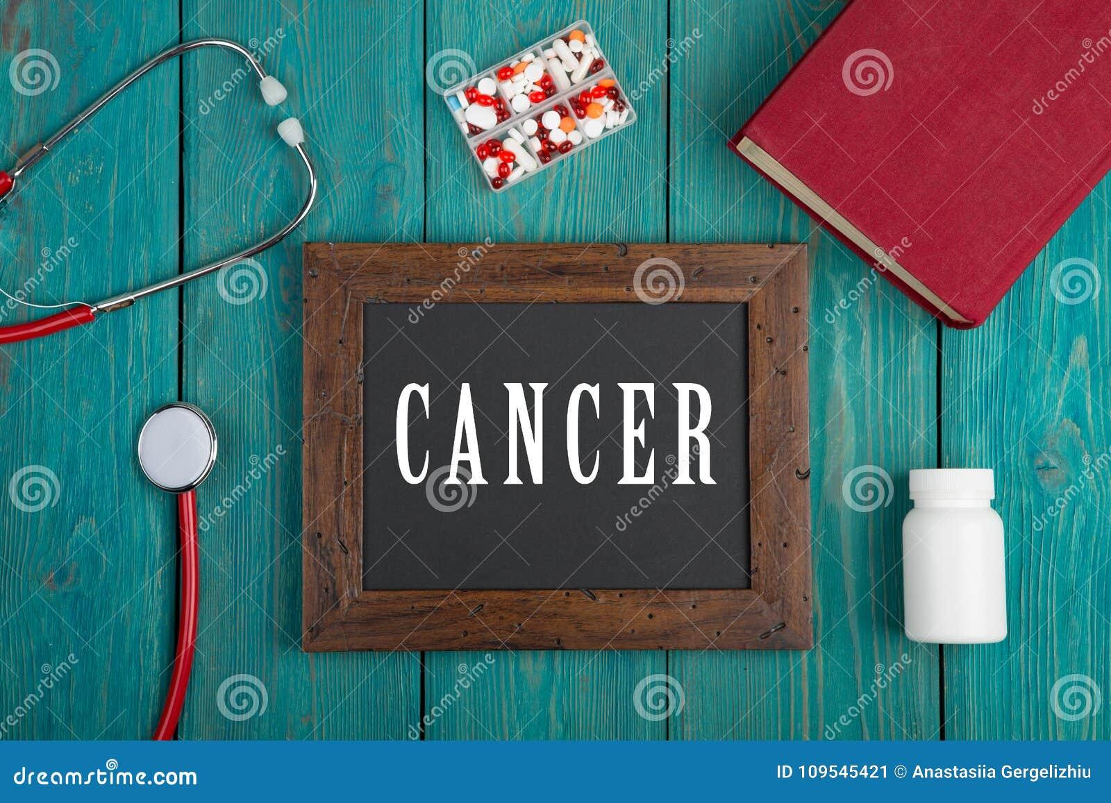Svart tavla med text & x22; Cancer& x22; , bok, preventivpillerar och stetoskop på blå träbakgrund
