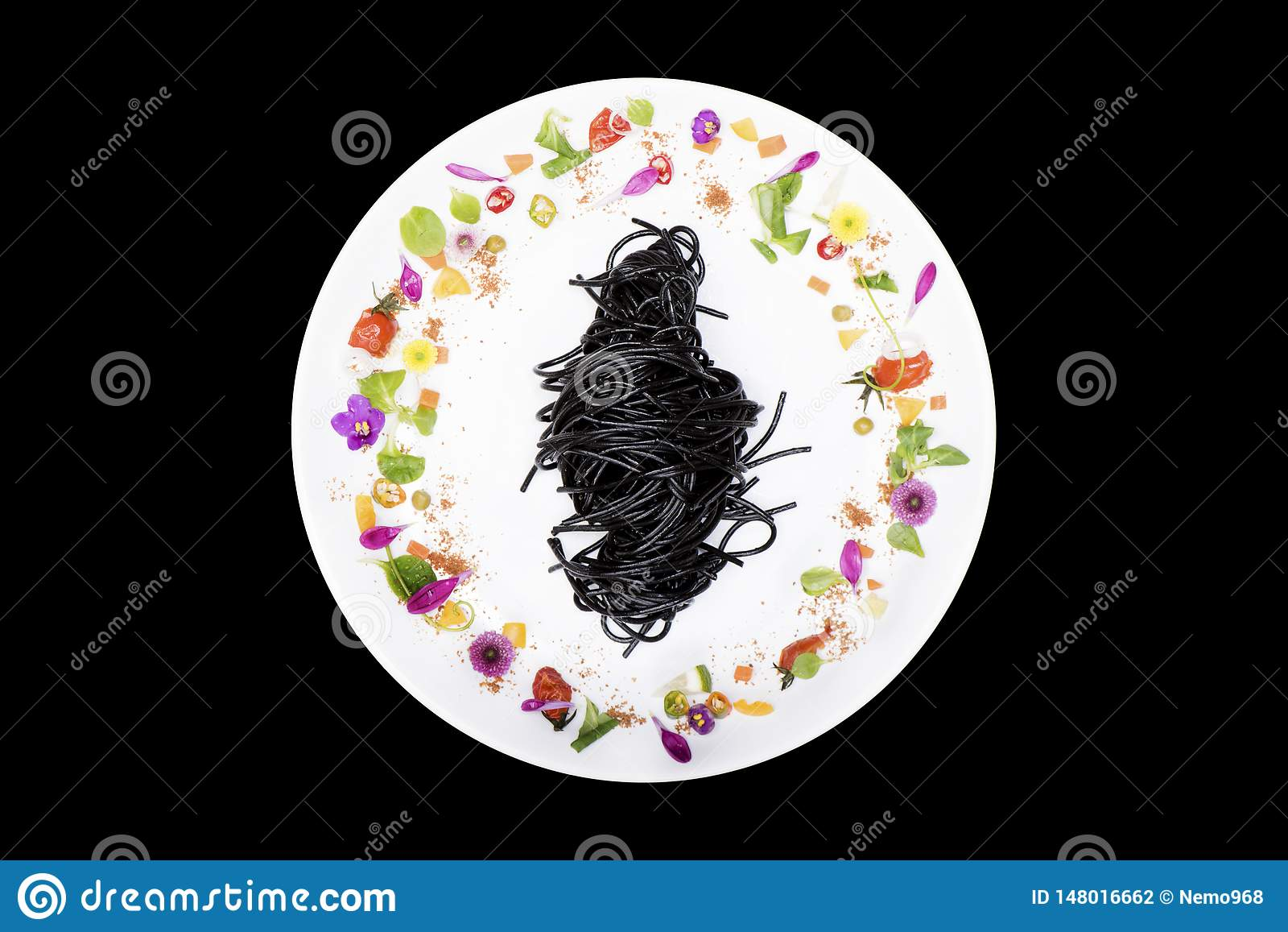 Svart tioarmad bläckfiskspagetti i platta med blommagarnering på svart bakgrund