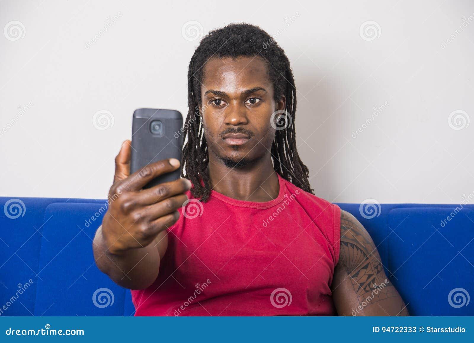 Svart ung man som tar selfiefotoet på soffan