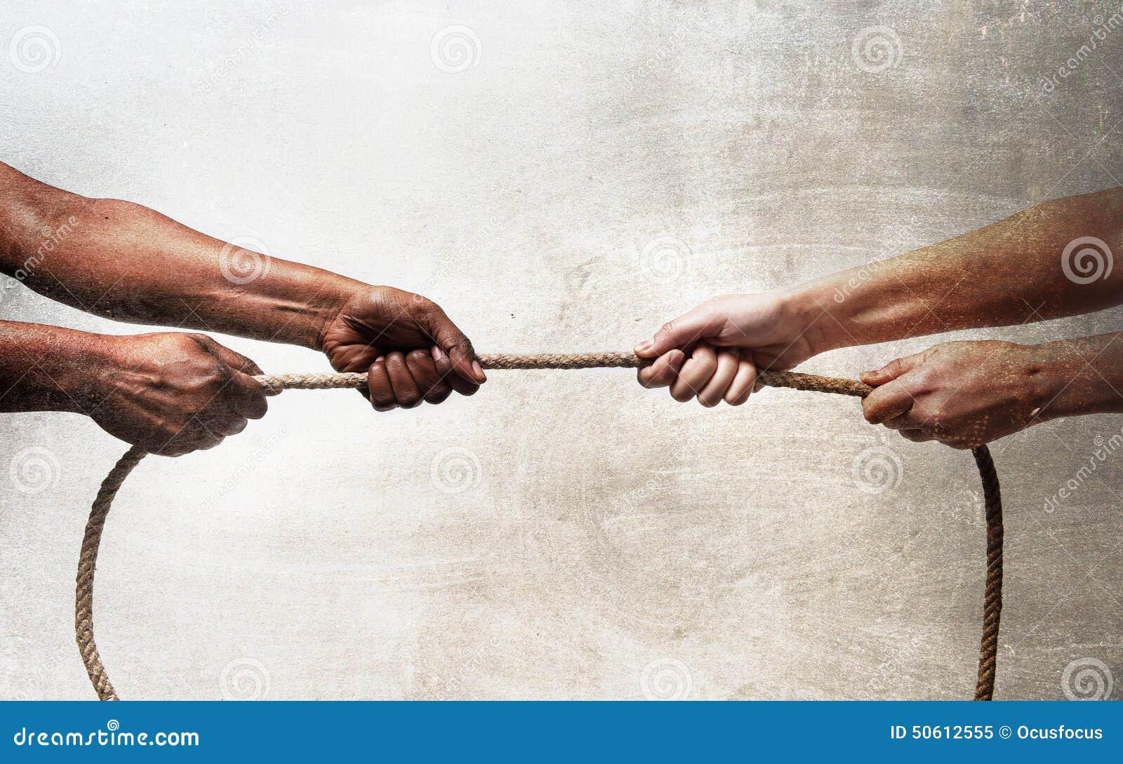 Svarta etnicitetarmar med det dragande repet för händer mot den vita Caucasian lopppersonen i stopprasism och xenofobibegrepp