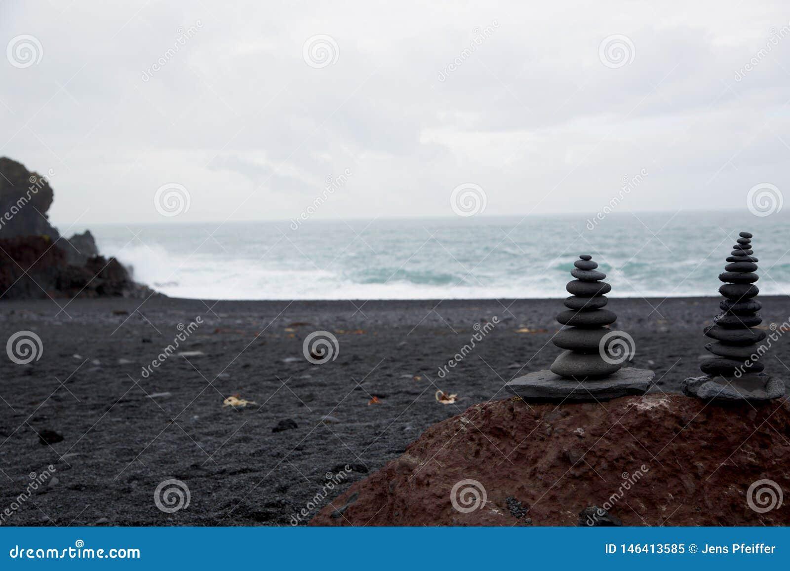 Svarta stenar på stranden för Djúpalà ³nssandur, Island