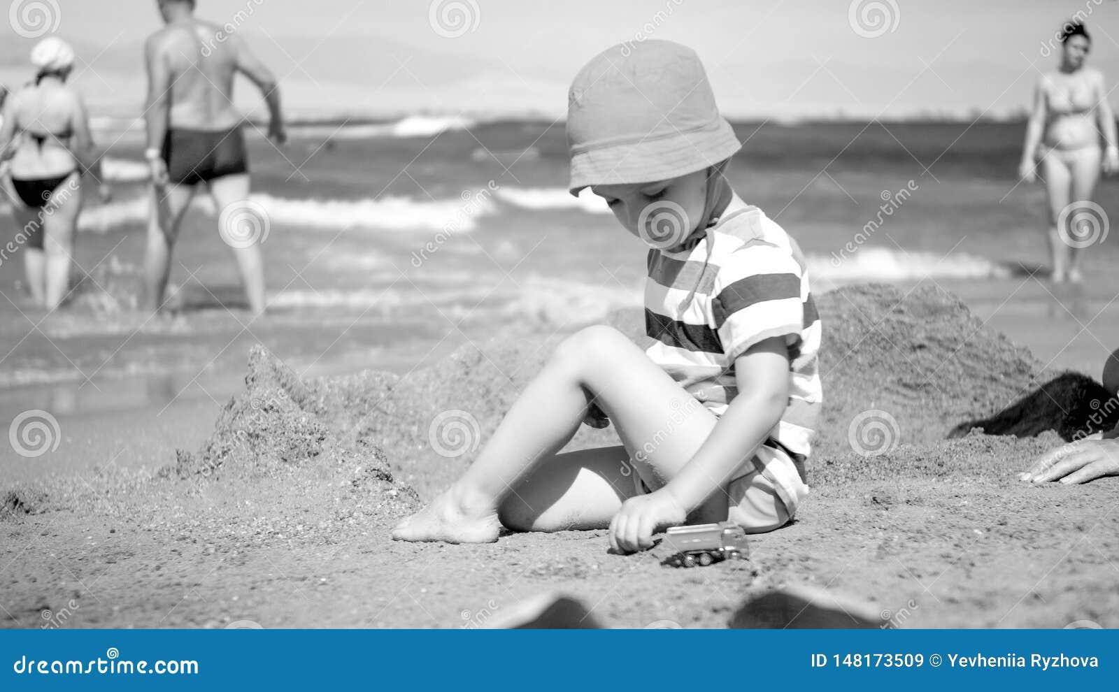 Svartvit bild av den gulliga litet barnpojken i hatten som sitter på havsstranden och spelar med leksakbilar Barn som kopplar av