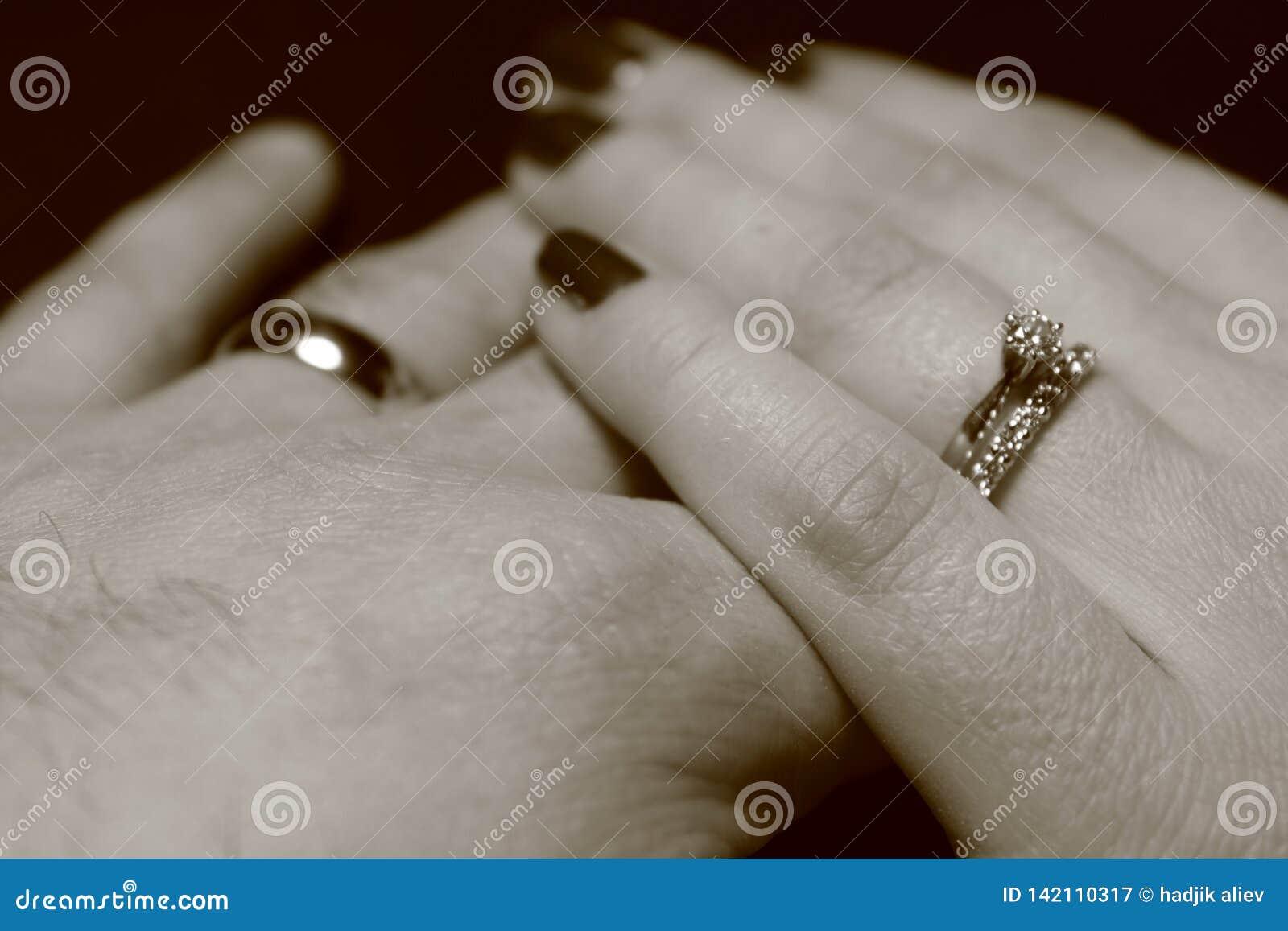 Svartvit bild av två händer som trycker sig på med vigselringar på svart bakgrund