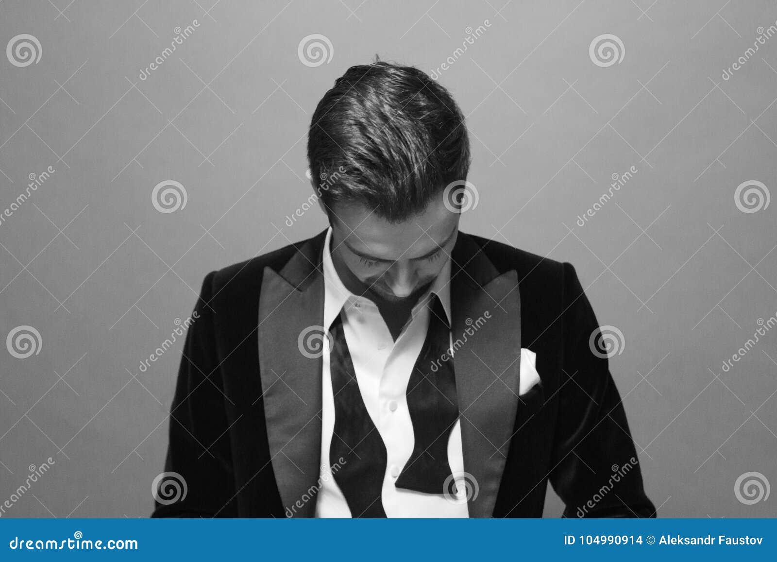Svartvit stående av en man i uppknäppta knappar för en dräkt, fluga- och skjorta
