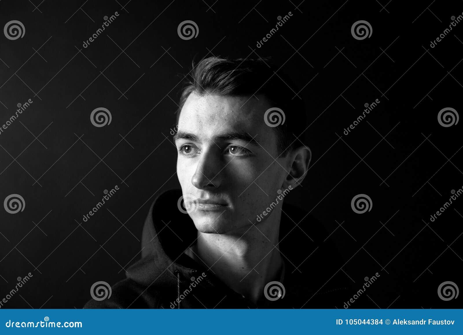 Svartvit stående av en ung man som ser till sidan, mot vanlig studiobakgrund