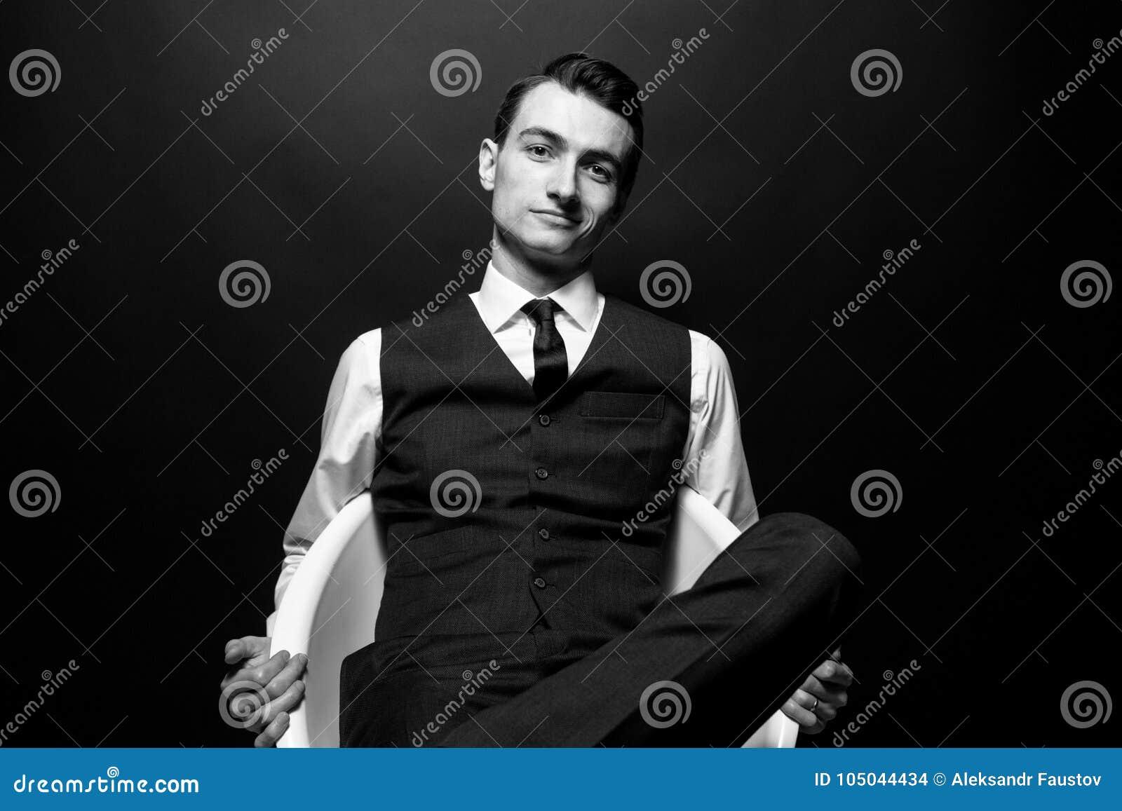 Svartvit stående av en ung stilig man i en vit skjorta, smoking och väst som ser kameran