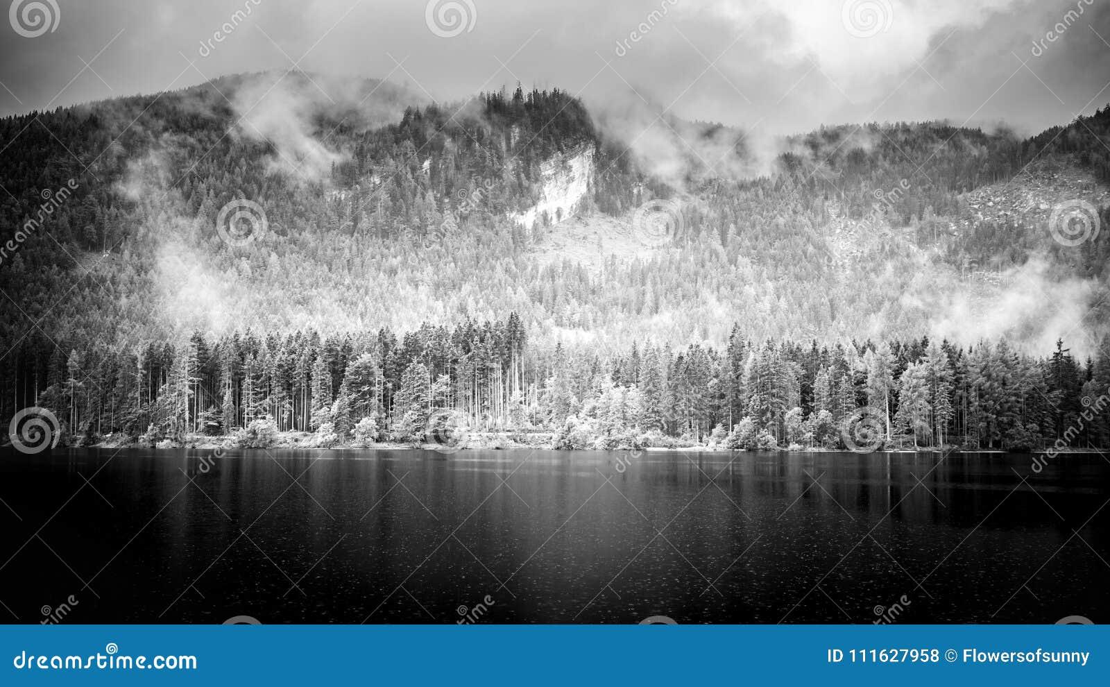 Svartvitt sjölandskap med berg Molnig och dimmig sikt, abstrakt naturpanorama