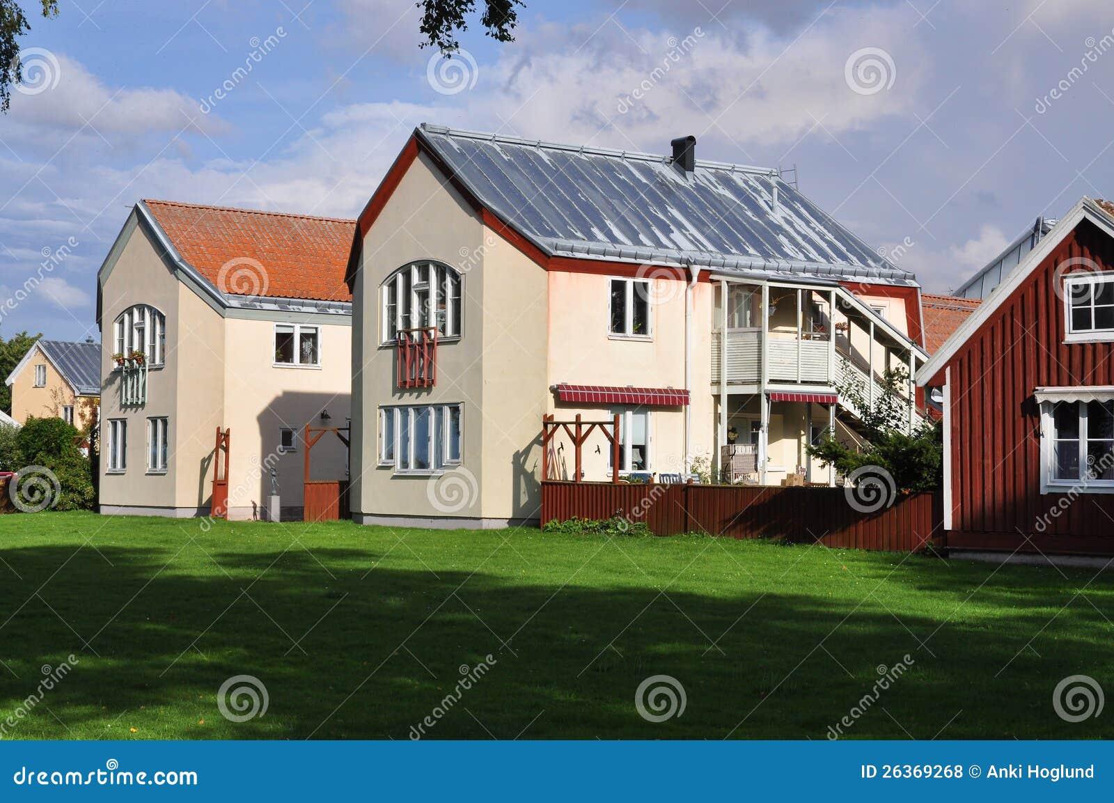 Svensk arkitektur, en röd stuga och två rappade aparmentbyggnader ...