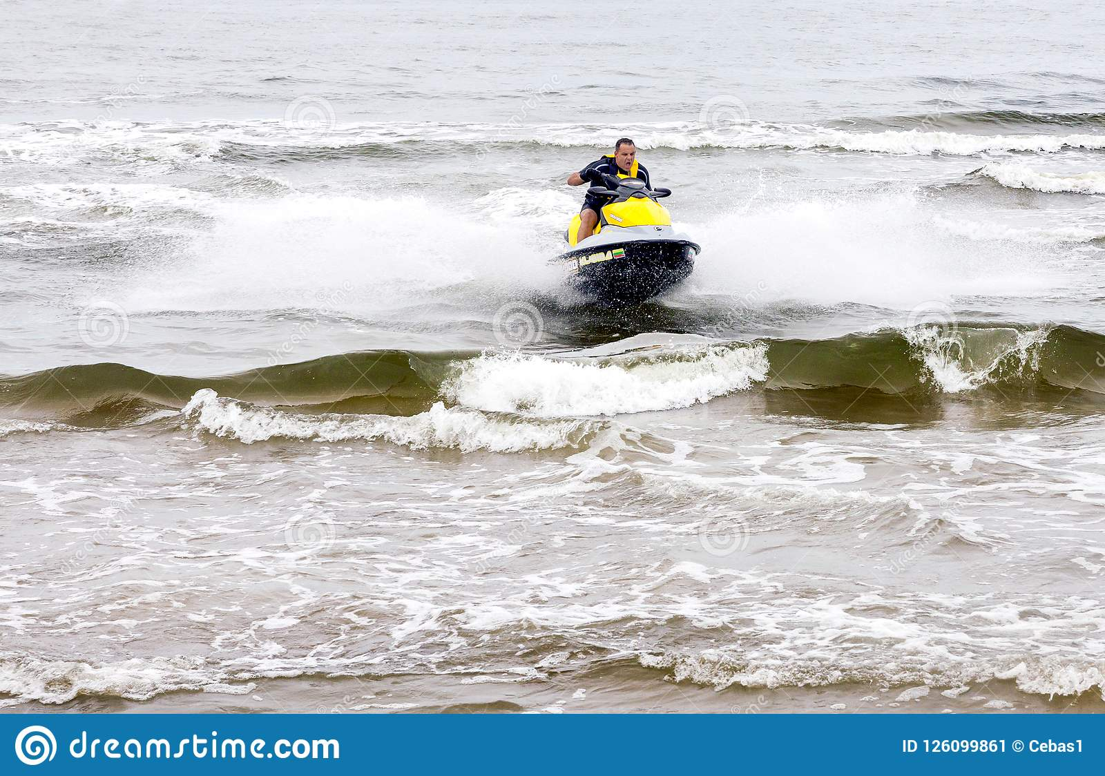 Young man performing tricks on jet ski on the sea waves