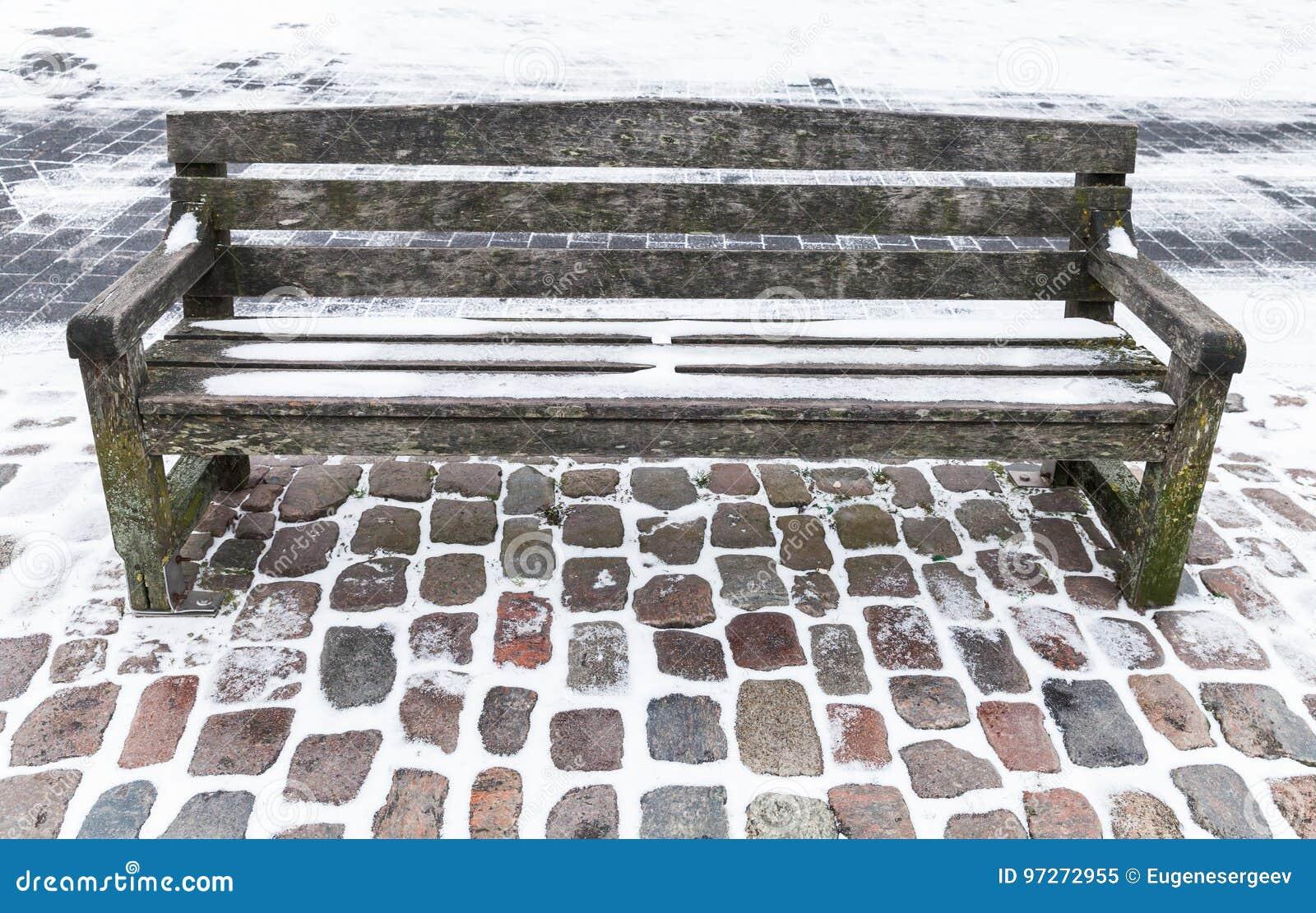 Svuoti il banco di legno coperto di neve nell inverno