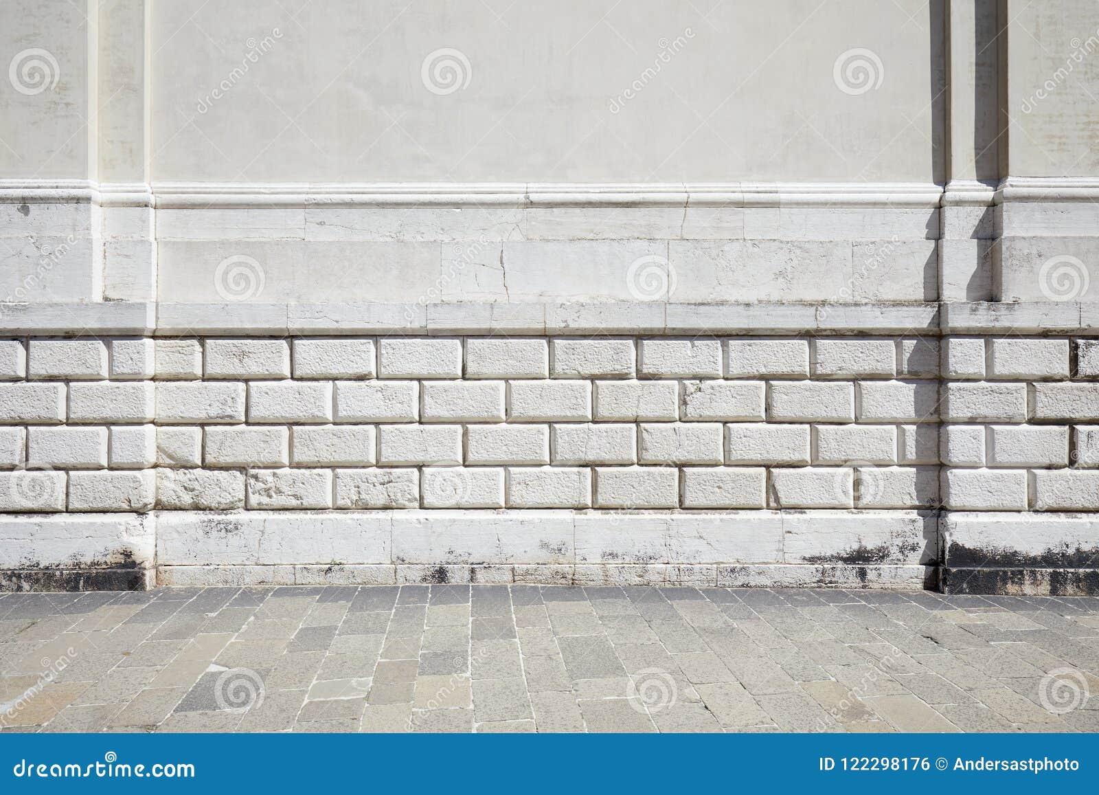 Svuoti il marciapiede di pietra piastrellato e la parete antica bianca