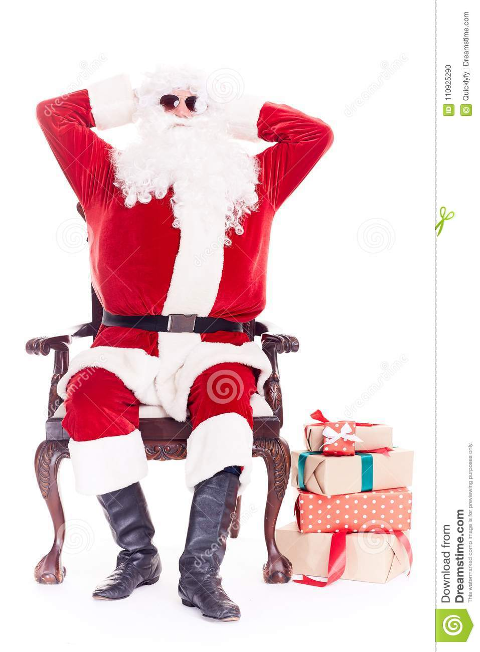 Portrait of swaggy santa claus in sunglasses relaxing in chair on white background