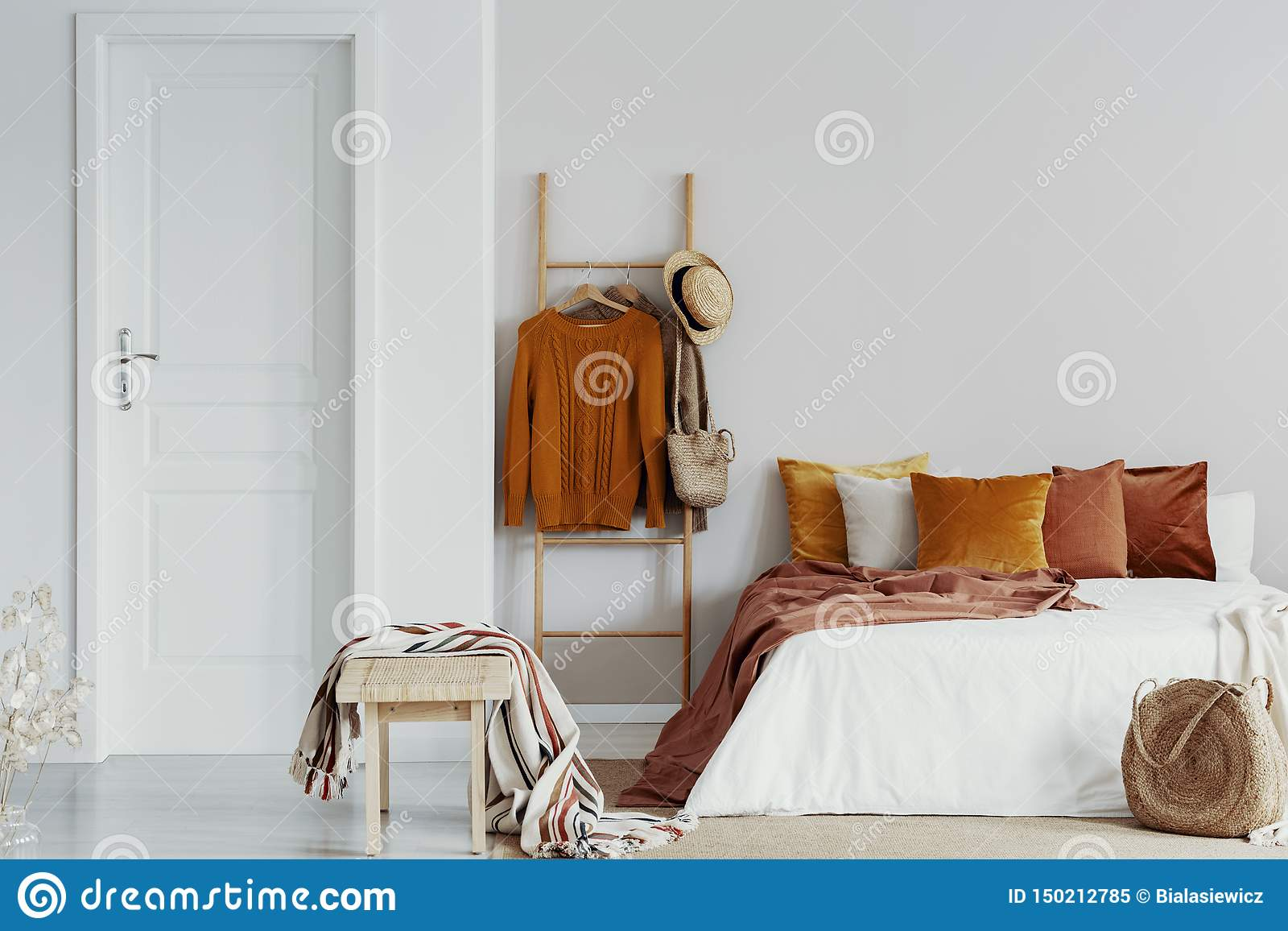 Sweaters Wicker Hat And Bag On Wooden Ladder Next To King Size Bed With Velvet Pillows In White Bedroom Interior Copy Space On Stock Image Image Of Copy Nightstand 150212785