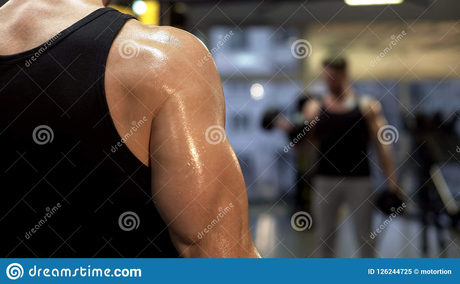 Sweaty sportsman pumping arm muscles, holding dumbbells in hands close up, goal