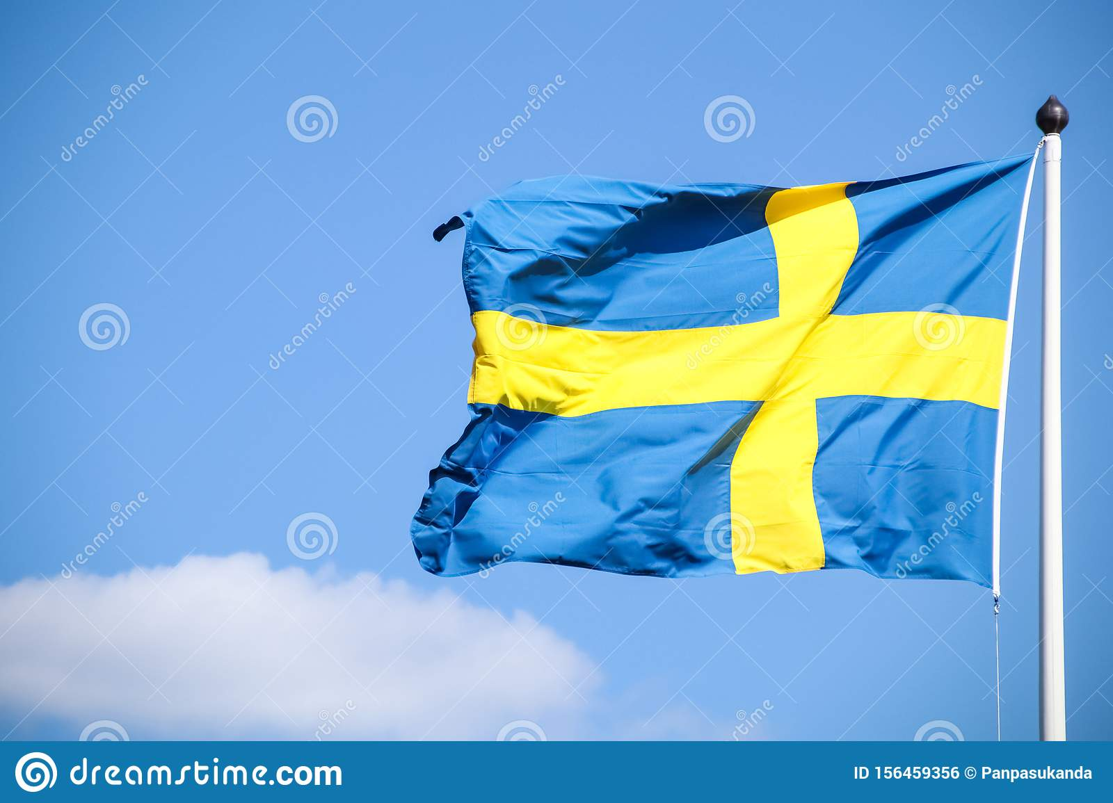 Sweden flag on a pole with beautiful sky background.