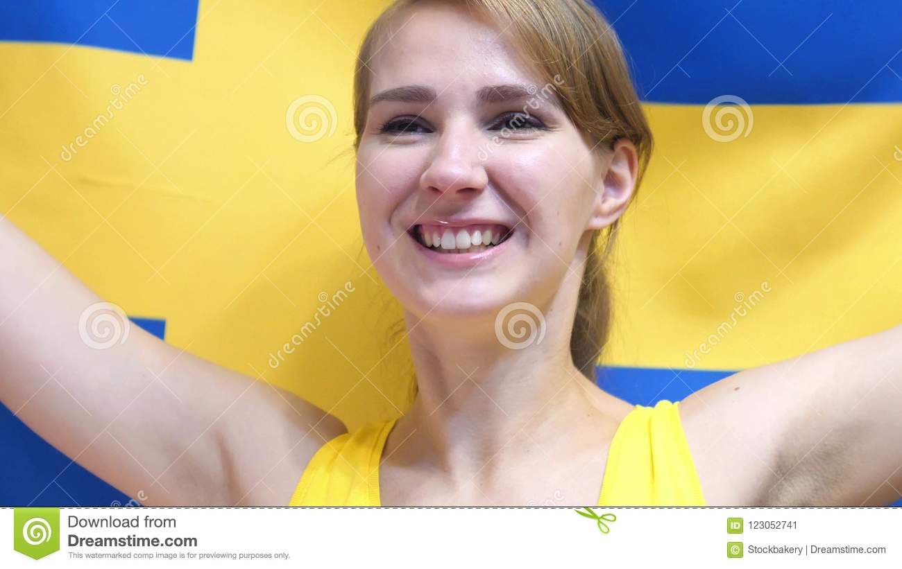 Swedish Young Woman Celebrating while holding the Flag of Sweden in Slow Motion