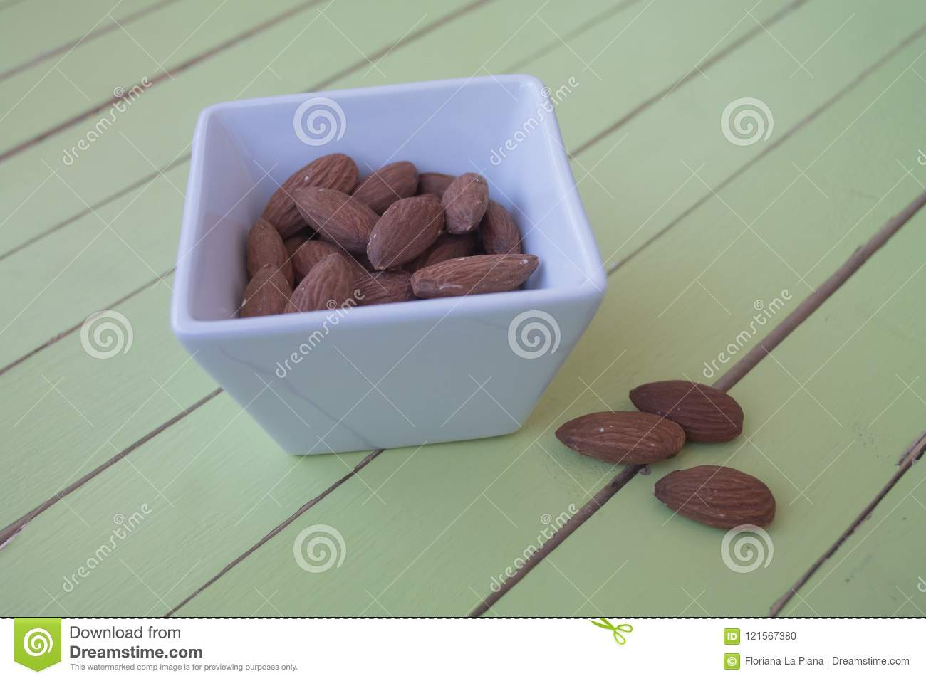 Sweet almonds in a white bowl on green wood