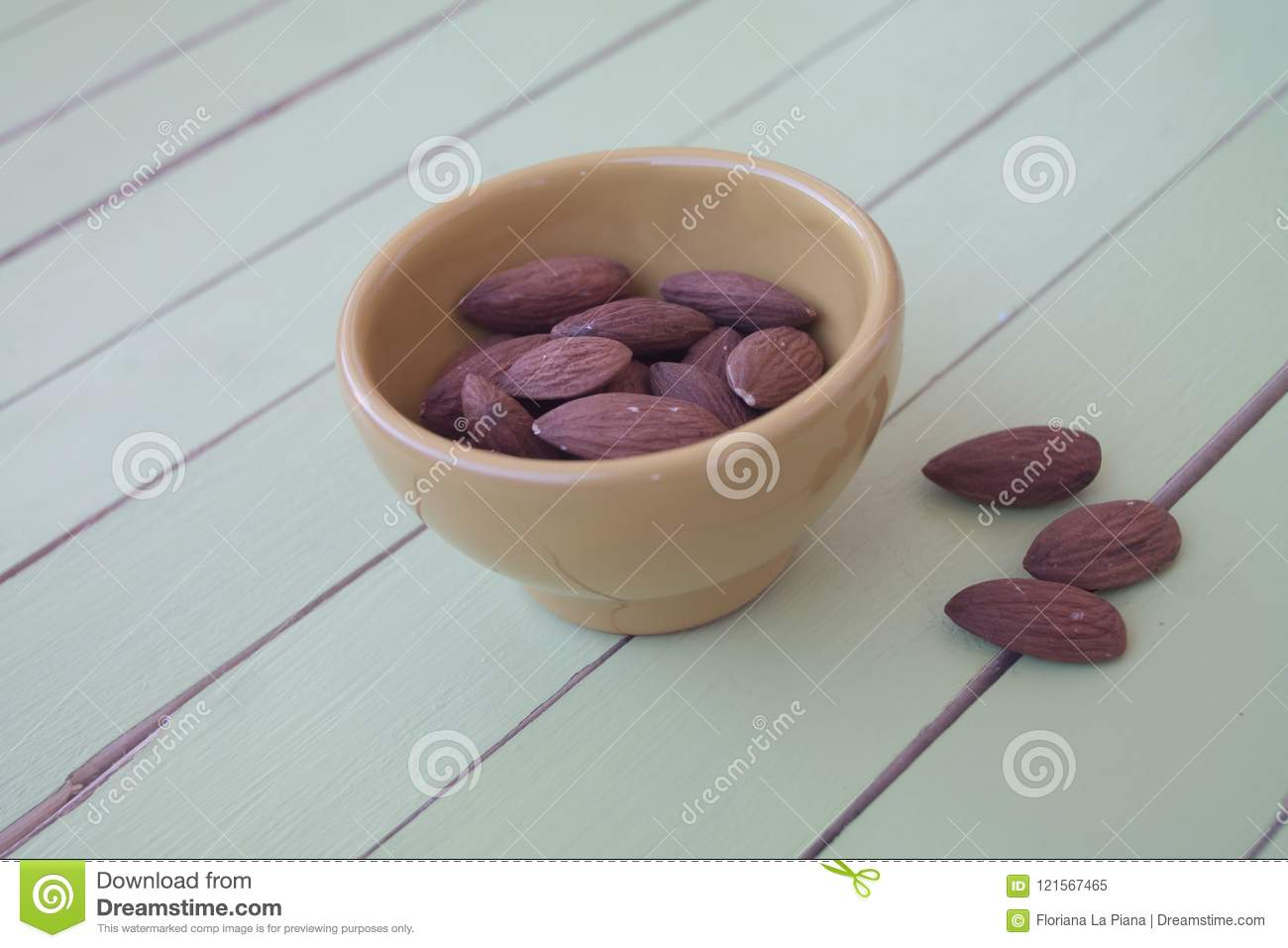 Sweet almonds in a yellow bowl on green wood