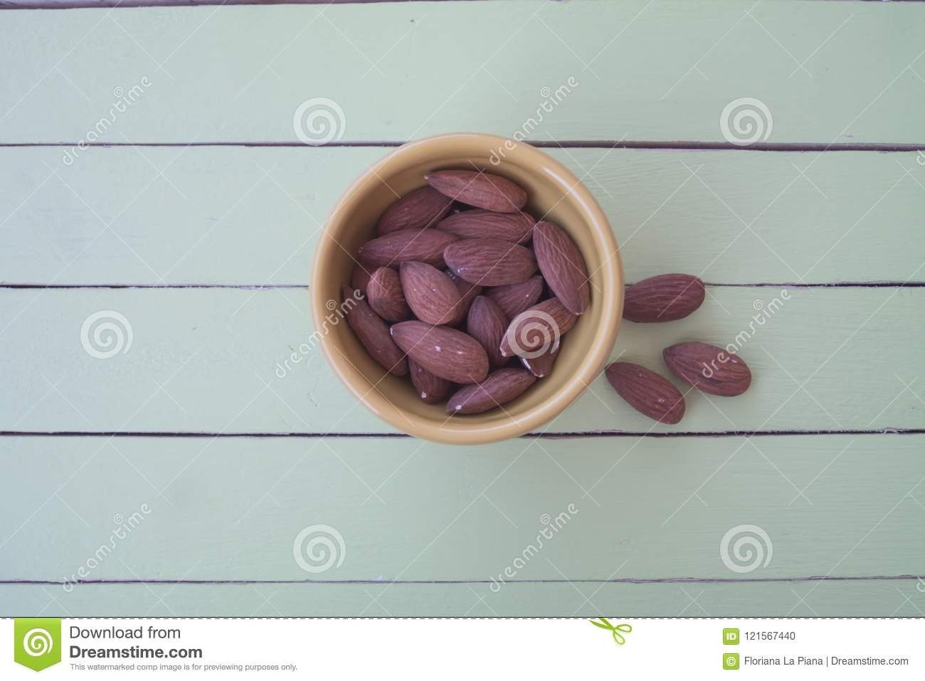 Sweet almonds in a yellow bowl on green wood from above