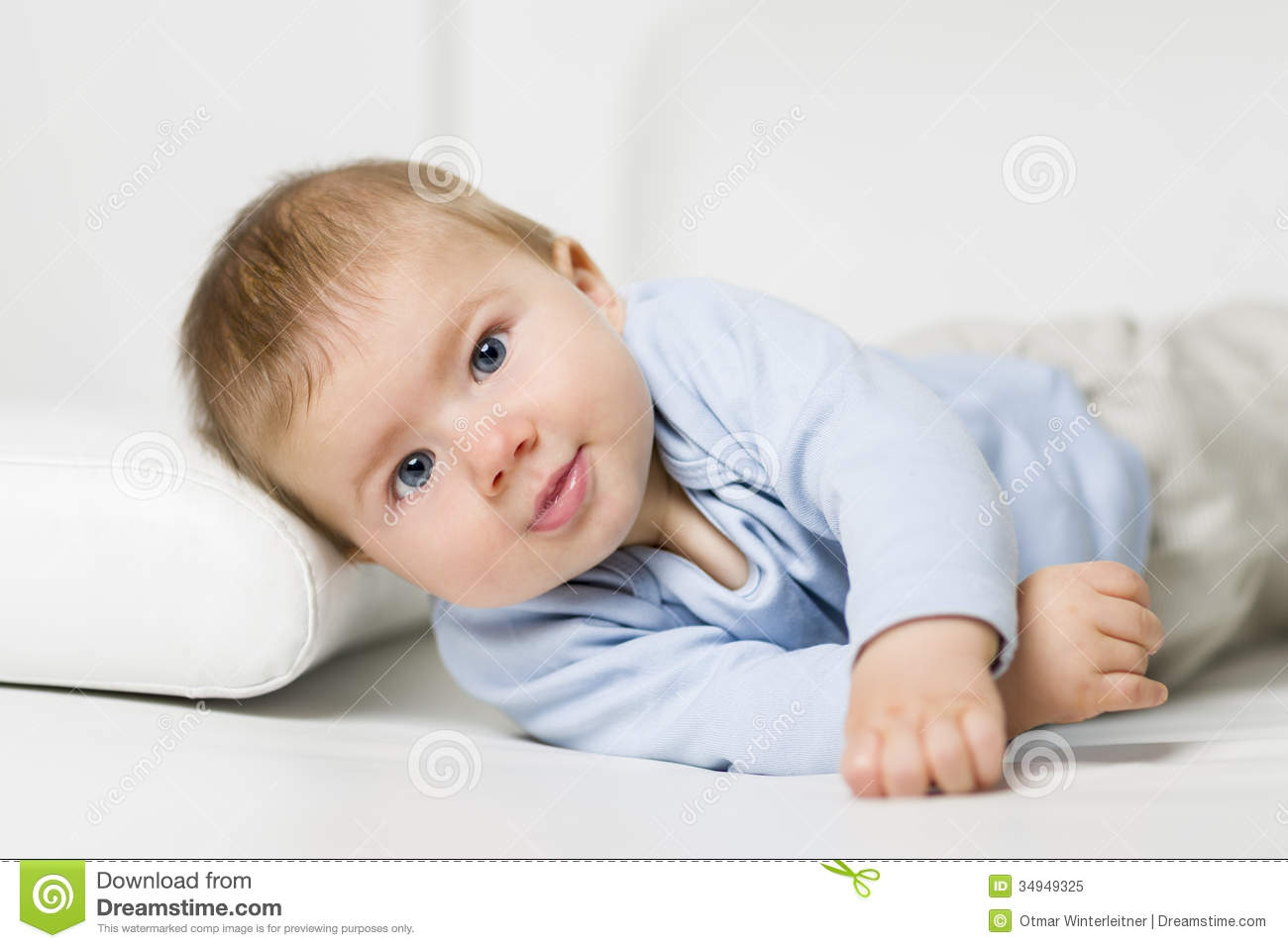 sweet baby boy lying on one side on the sofa. stock image - image of