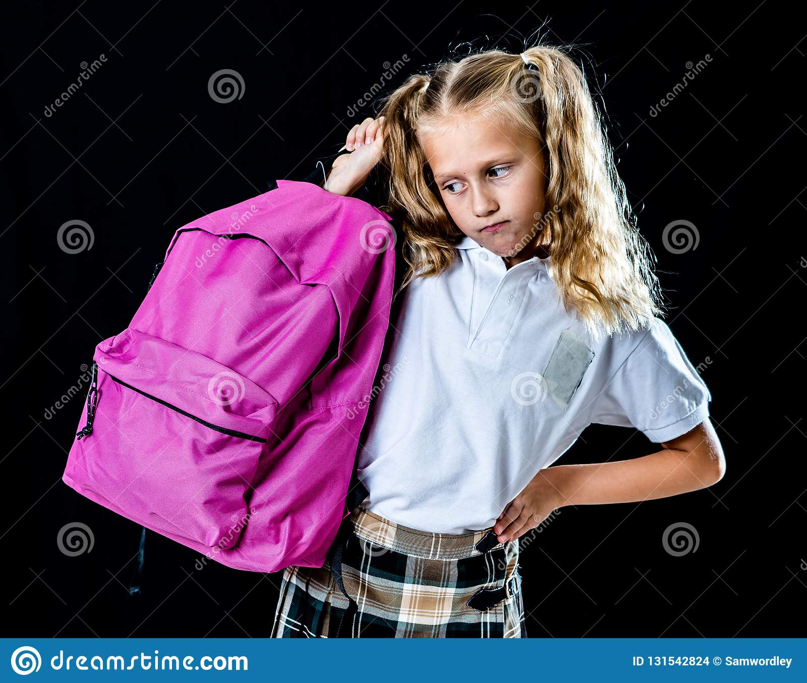 Sweet beautiful little girl in school uniform feeling angry and frustrated looking at the camera isolated on black background in
