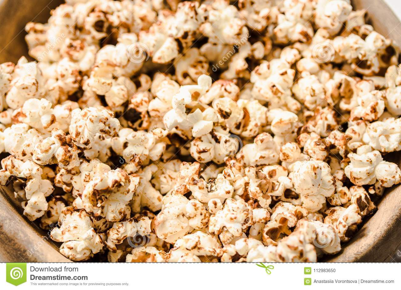 Sweet caramel vegan popcorn in a wooden plate. Snack for the movie. Rustic.light background. Macro. Top view.