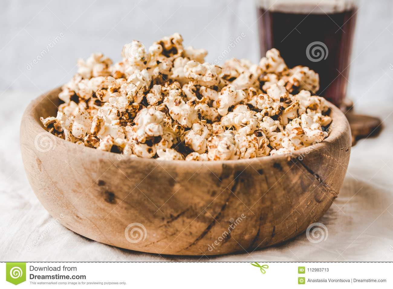 Sweet caramel vegan popcorn in a wooden plate. Snack for the cinema. Rustic.light background. Selective focus. Toning.