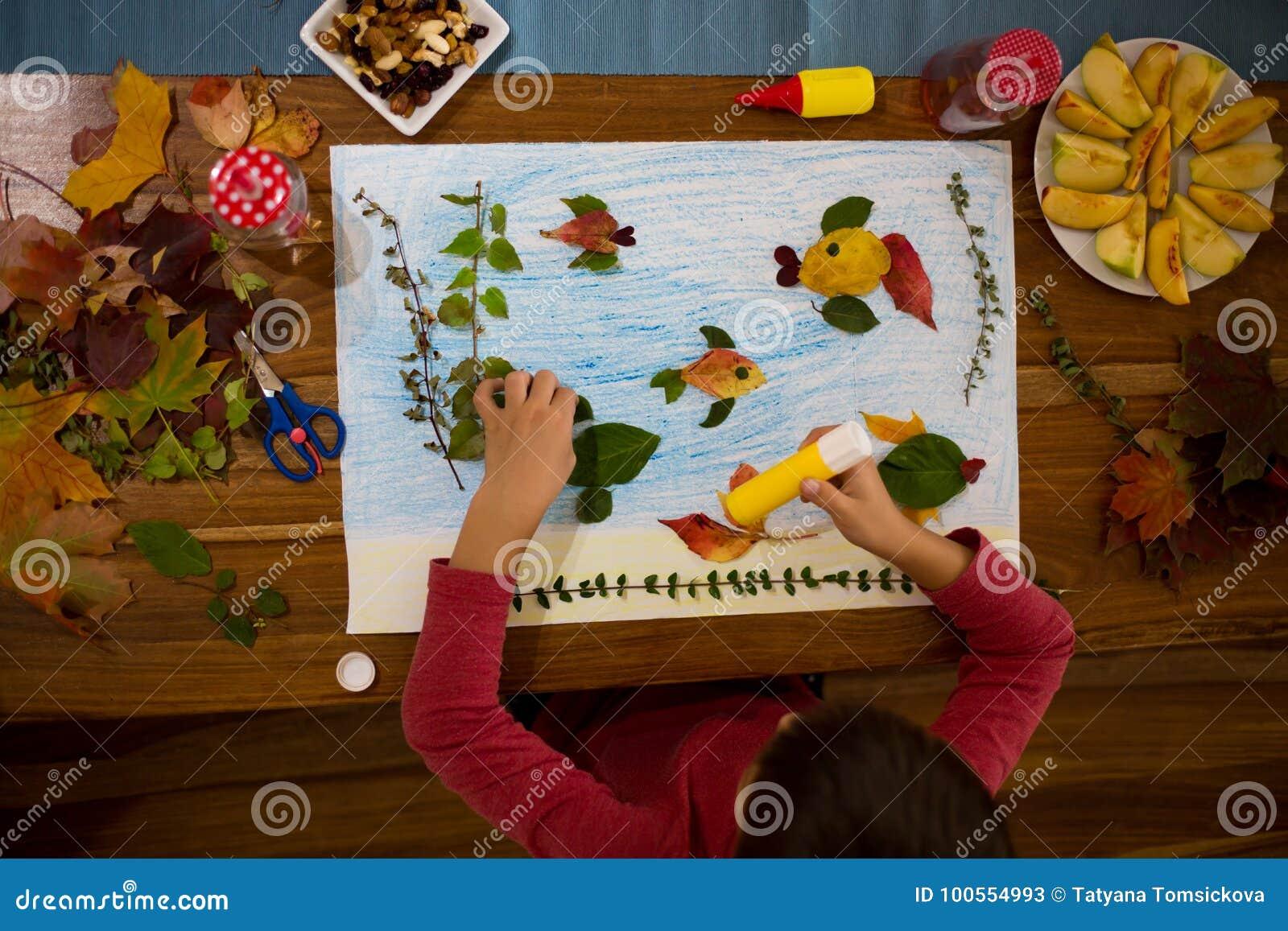 Sweet Child Boy Applying Leaves Using Glue Stock Image