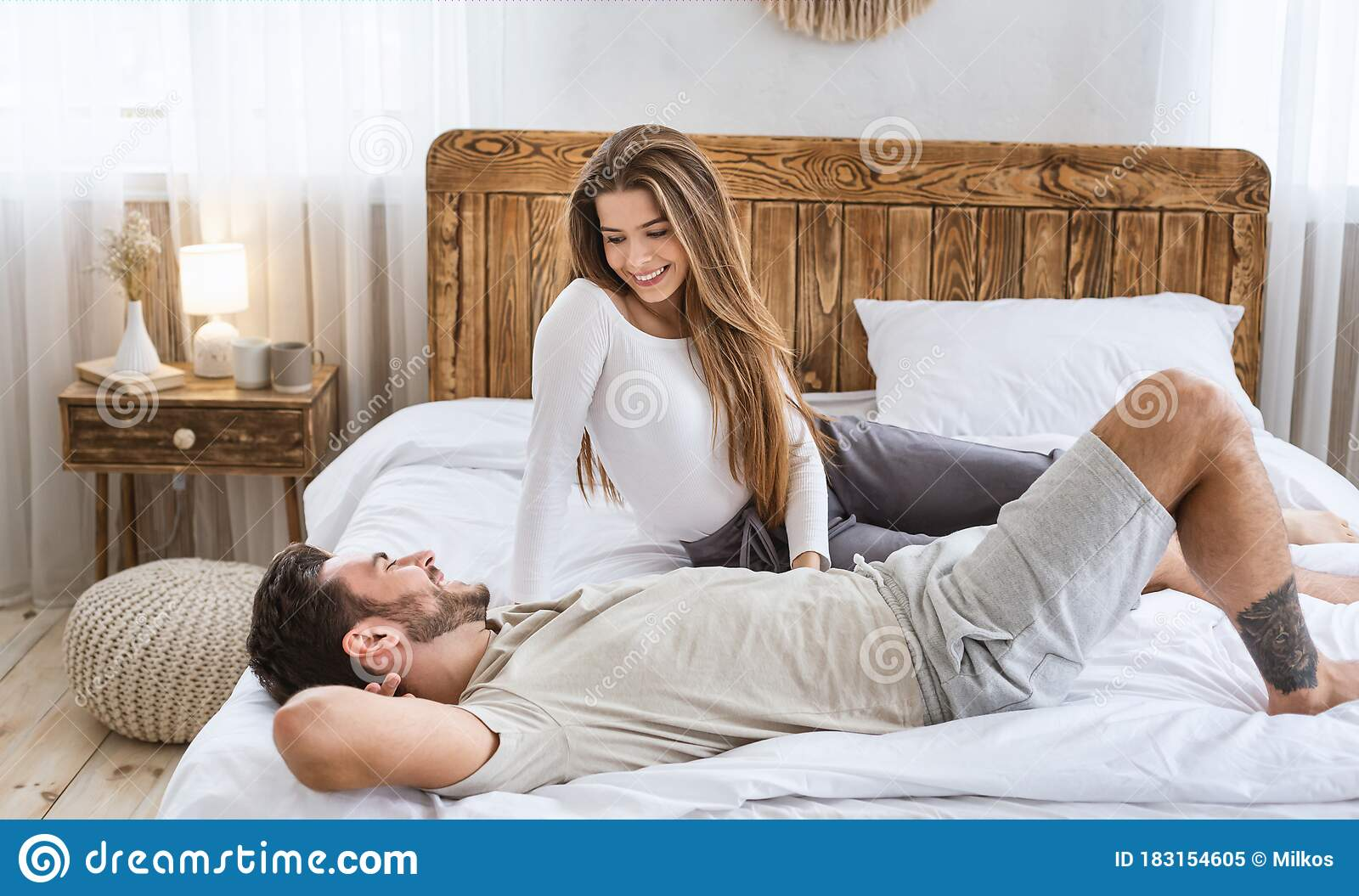Man And Woman Talking In Bed In Bedroom Interior Stock