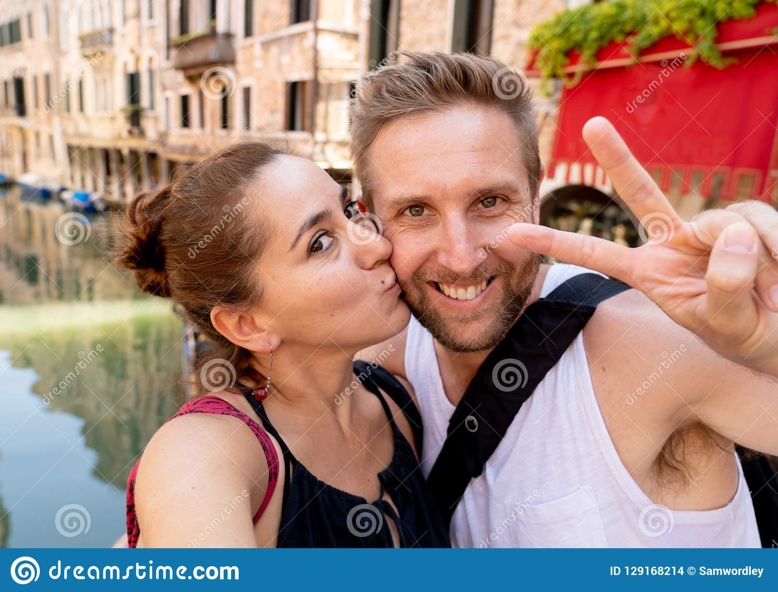 Sweet couple in love taking a selfie in Venice Italy while traveling around europe