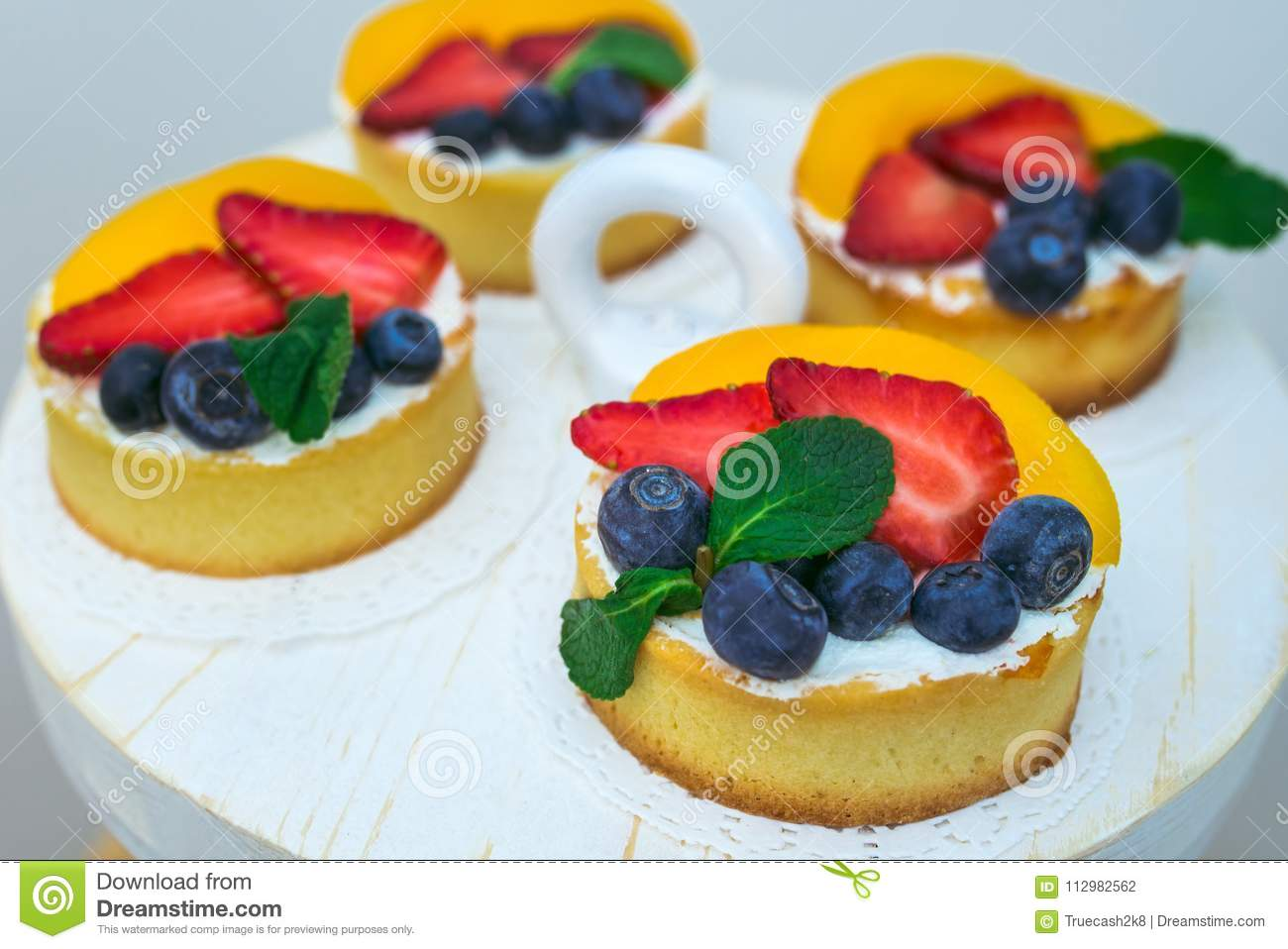 Sweet Delicious biscuit cakes with fresh strawberries and blueberries beautifully decorated