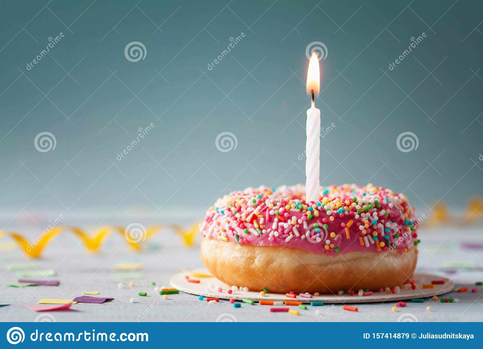 Sweet donut and one burning candle. Happy birthday concept
