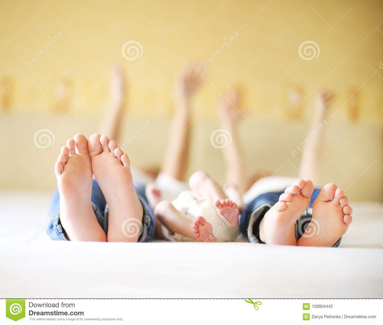Sweet family in bed. Three sisters, close up on feet