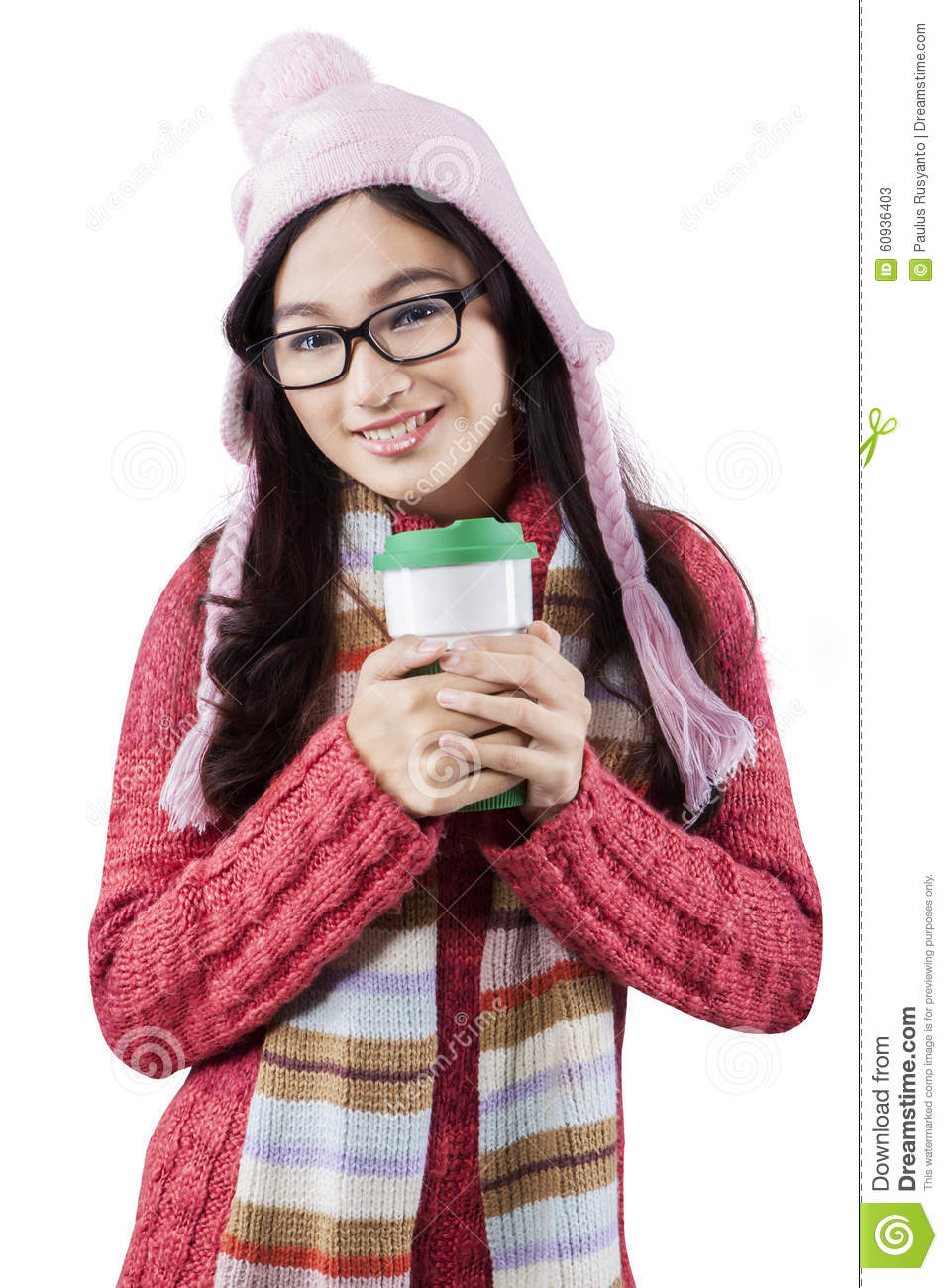 f24574cb3 Portrait of teenage girl wearing winter wear, smiling at the camera while  holding a cup of hot drink