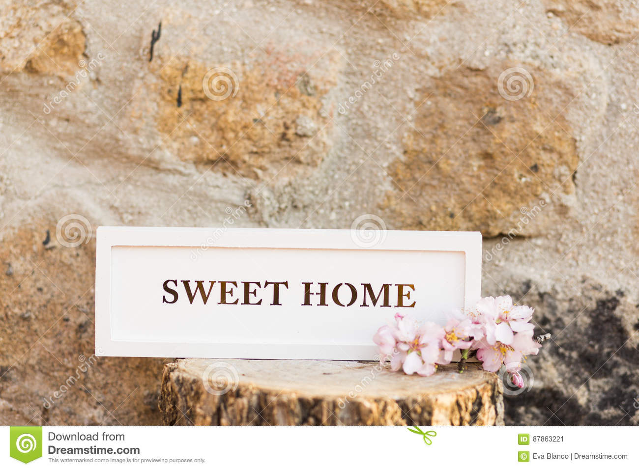 Sweet home sign on a wood trunk. Stone wall background