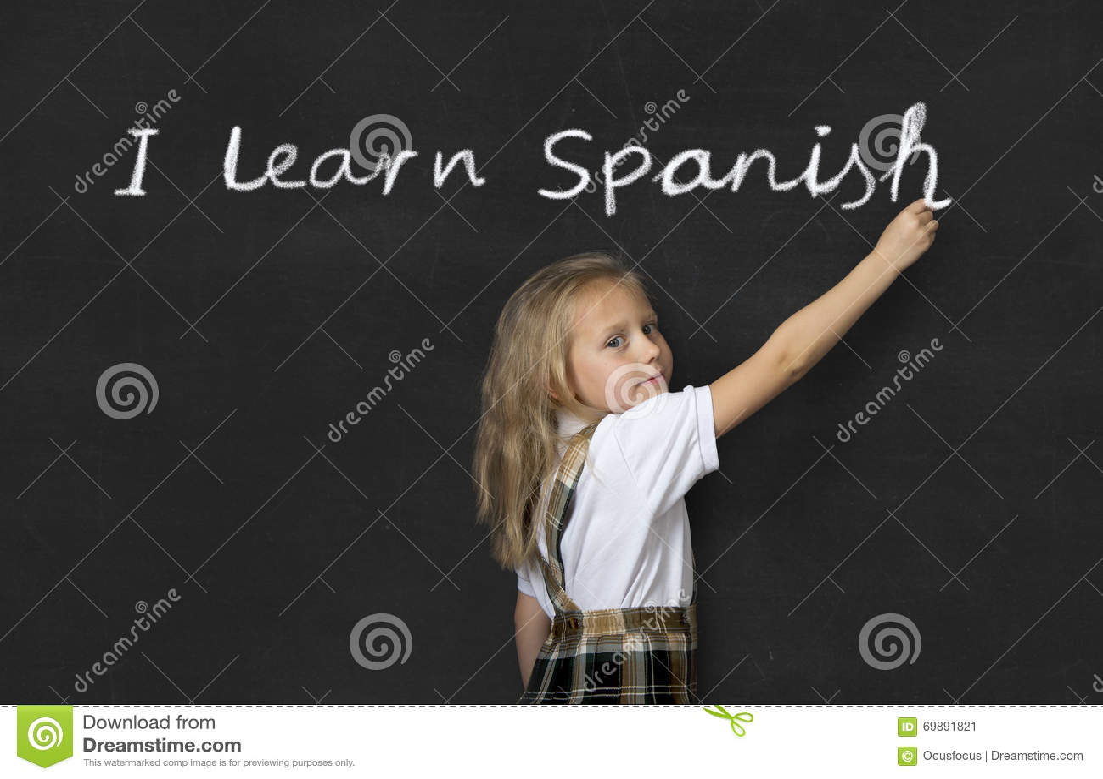 Sweet junior schoolgirl standing happy writing in blackboard I learn Spanish